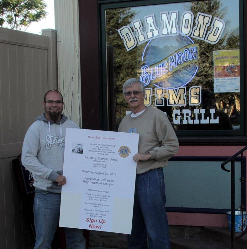 Nick Theis, left, event chairman, and Jim McClung, president of the Dundee Township Lions Club, post signs inside Diamond Jim's for the annual charity beanbag tournament.