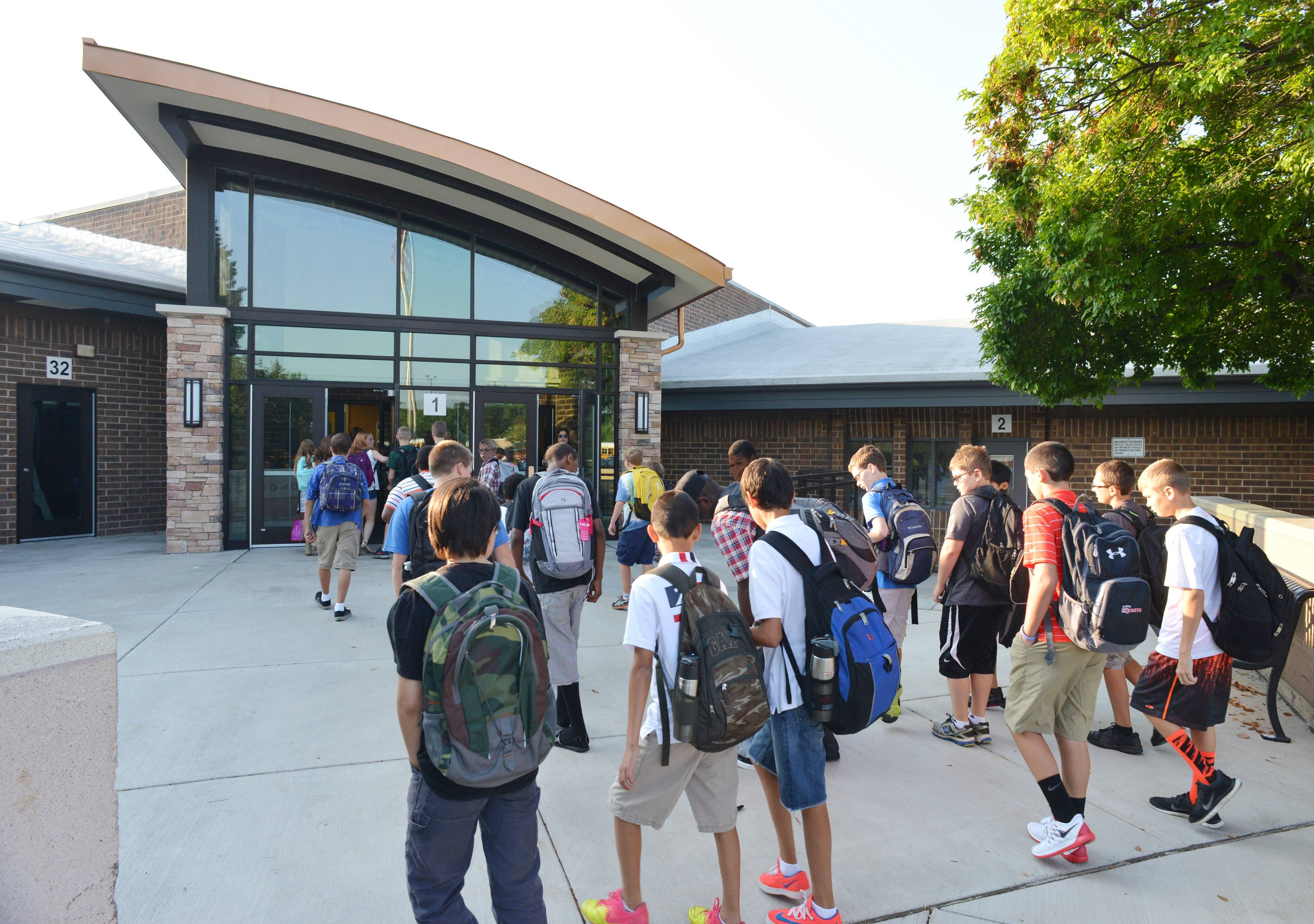 Students converge on Madison Junior High School in Naperville for the first day of classes Wednesday in Naperville Unit District 203. The school got a $769,000 front entrance and vestibule this summer to increase safety.