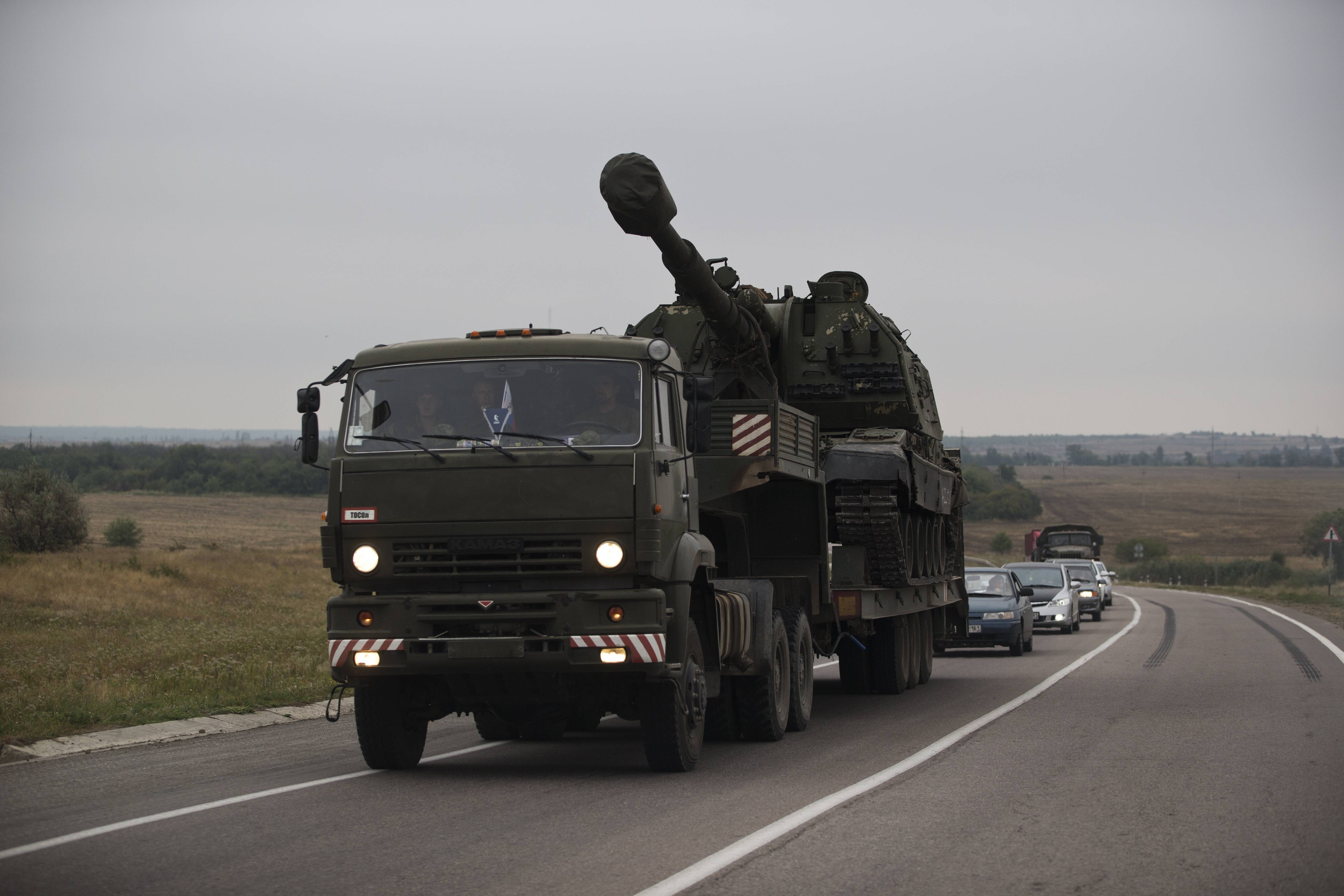 A Russian military truck carries a MSTA-S self-propelled howitzer about 10 kilometers from the Russia-Ukrainian border control point at town Donetsk, Rostov-on-Don region, Russia, Tuesday, Aug. 19, 2014.
