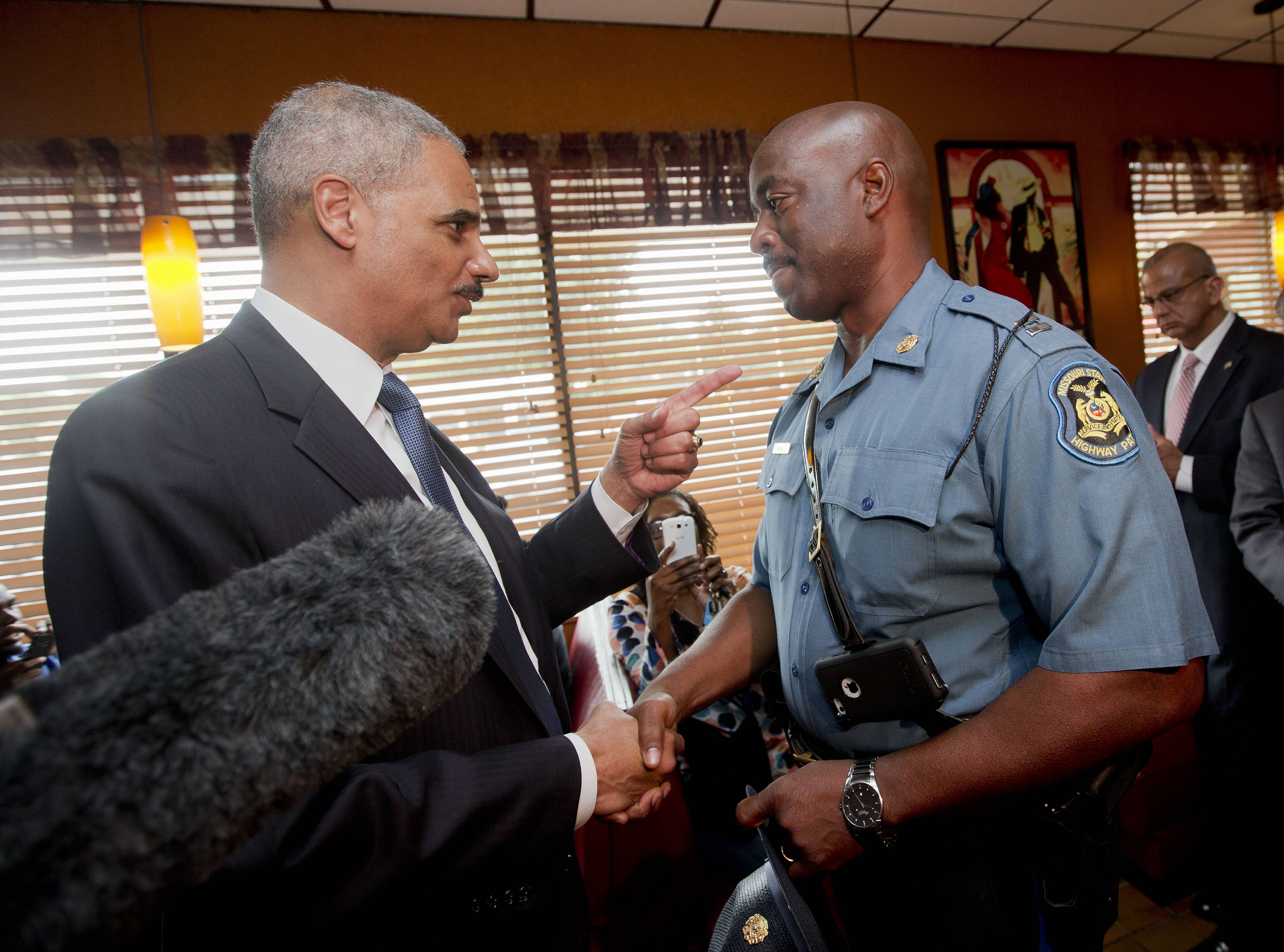 Attorney General Eric Holder talks with Capt. Ron Johnson of the Missouri State Highway Patrol on Wednesday in Florrissant, Mo.