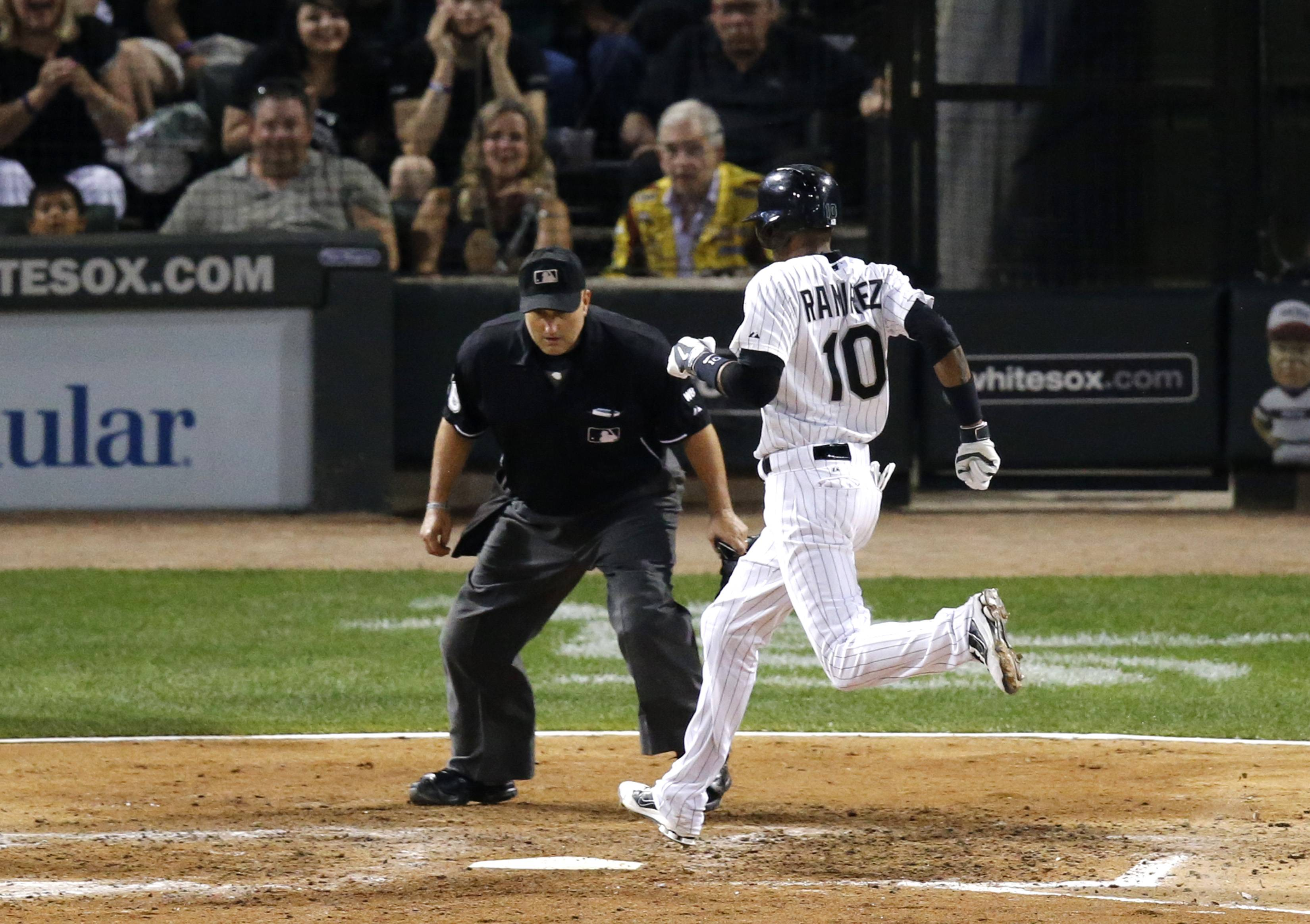 Home plate umpire Eric Cooper watches Chicago White Sox's Alexei Ramirez score on a sacrifice fly by Avisail Garcia, off a pitch from Baltimore Orioles' Wei-Yin Chen during the sixth inning of a baseball game Wednesday in Chicago.