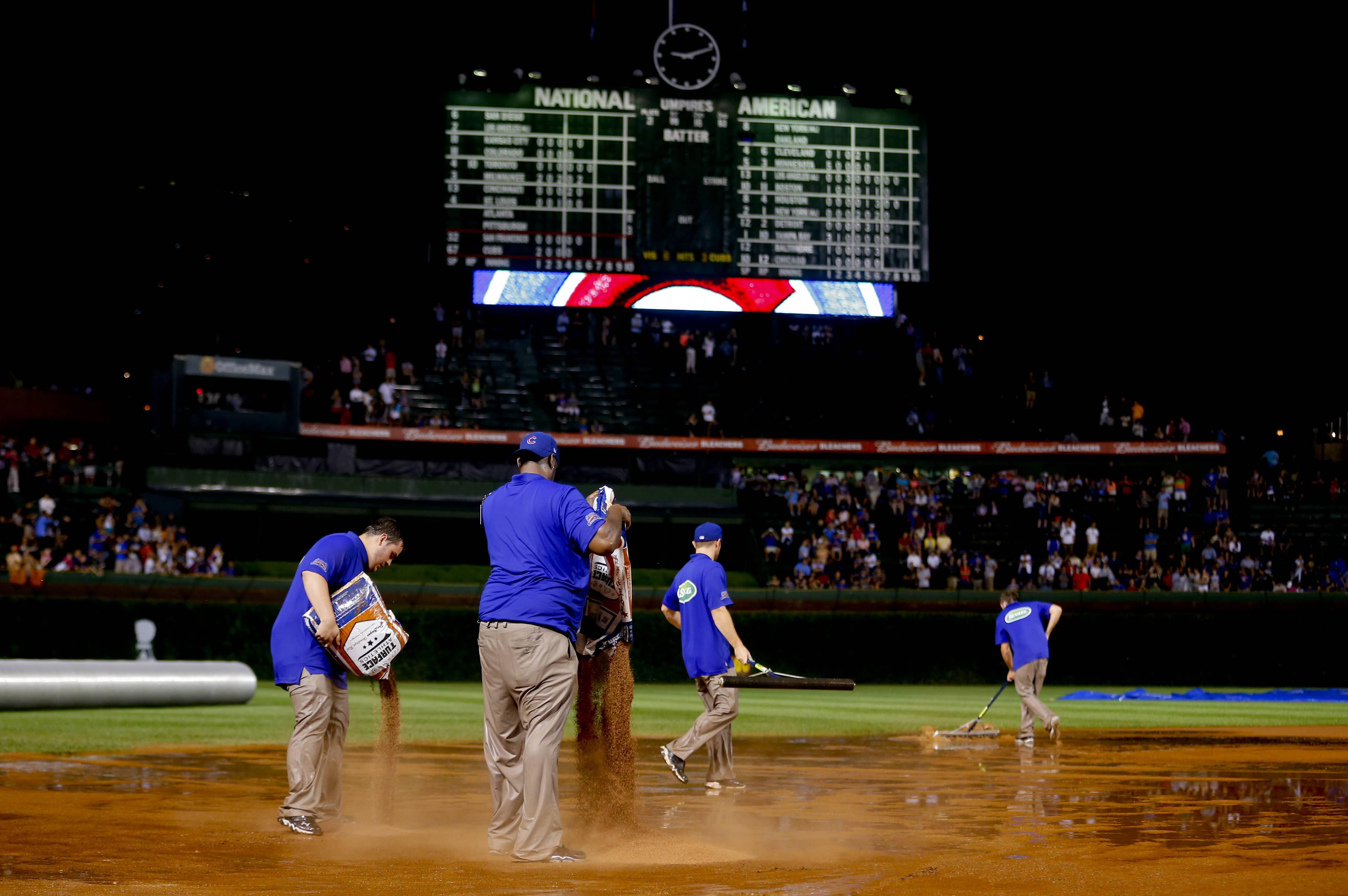 The grounds crew works on the field after a heavy rain soaked Wrigley Field during the fifth inning of a baseball game between the San Francisco Giants and the Chicago Cubs on Tuesday in Chicago. The Giants launched a successful protest after the Cubs were declared the winner. The game will resume Thursday.