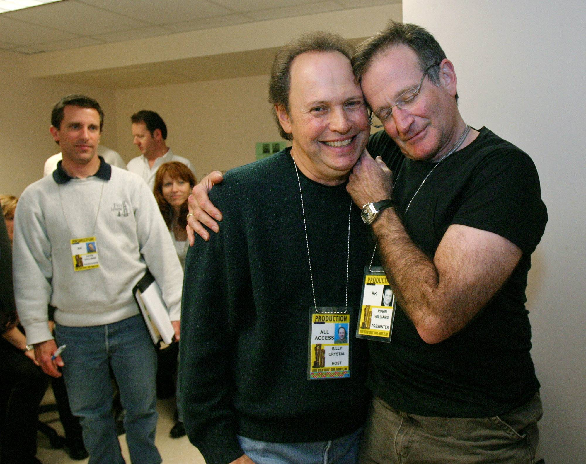 "FILE - This Feb. 28, 2004 file photo shows Oscar host Billy Crystal, center, and presenter Robin Williams, right, joking around after a writers' meeting for the 76th annual Academy Awards in Los Angeles. The producer of the Emmys says that Billy Crystal will pay tribute to Robin Williams during the awards ceremony. Executive producer Don Mischer said that Crystal will honor Williams as part of the traditional ""in memoriam"" segment for industry members who died during the past year. Williams was found dead by suicide in his Northern California home Aug. 11."