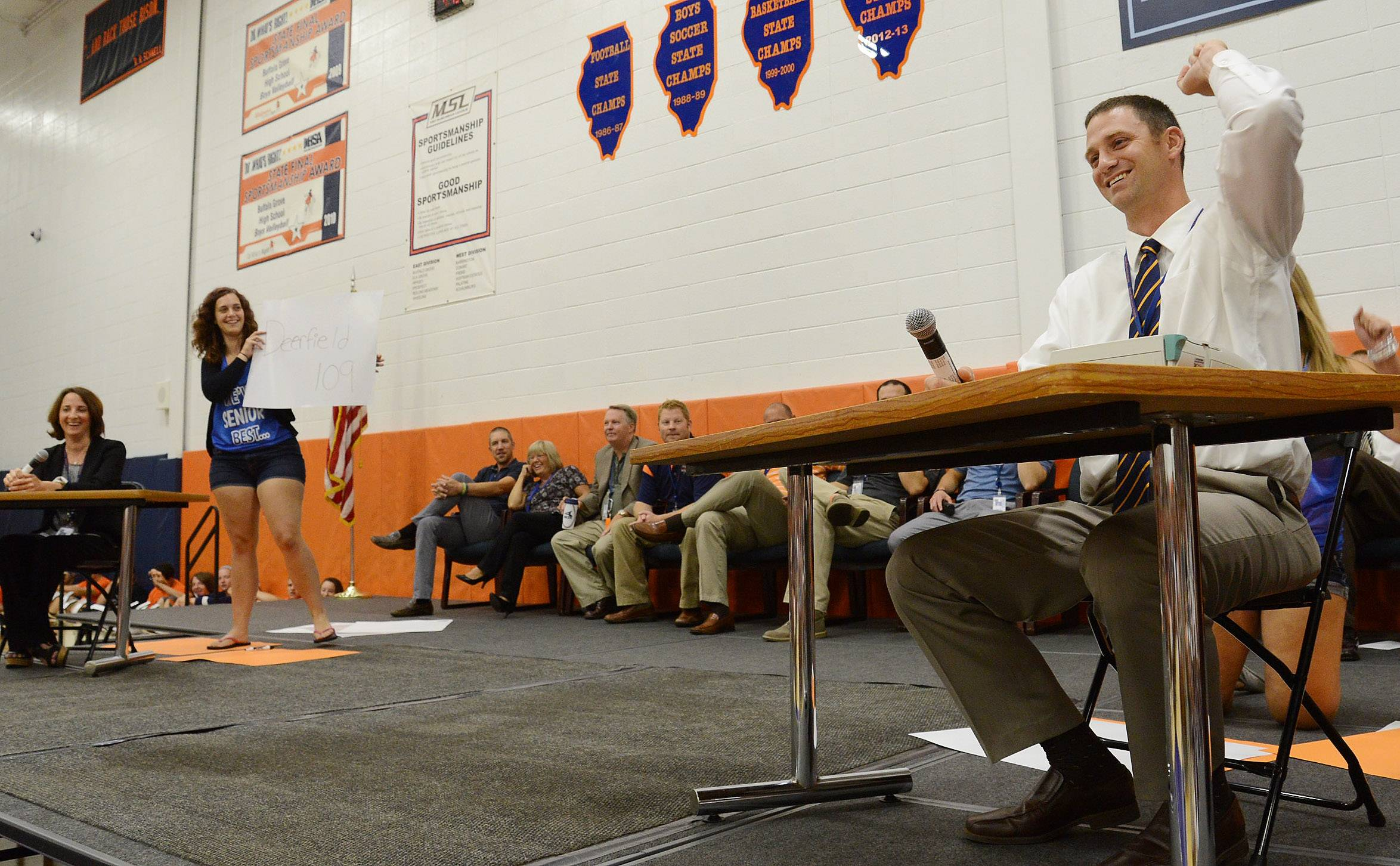 New Buffalo Grove High School principal Jeff Wardle, right, and associate principal Jill Maraldo, far left, compete in a game show, answering questions about themselves and how much knowledge they have of Buffalo Grove High School, during a back-to-school pep rally Wednesday.