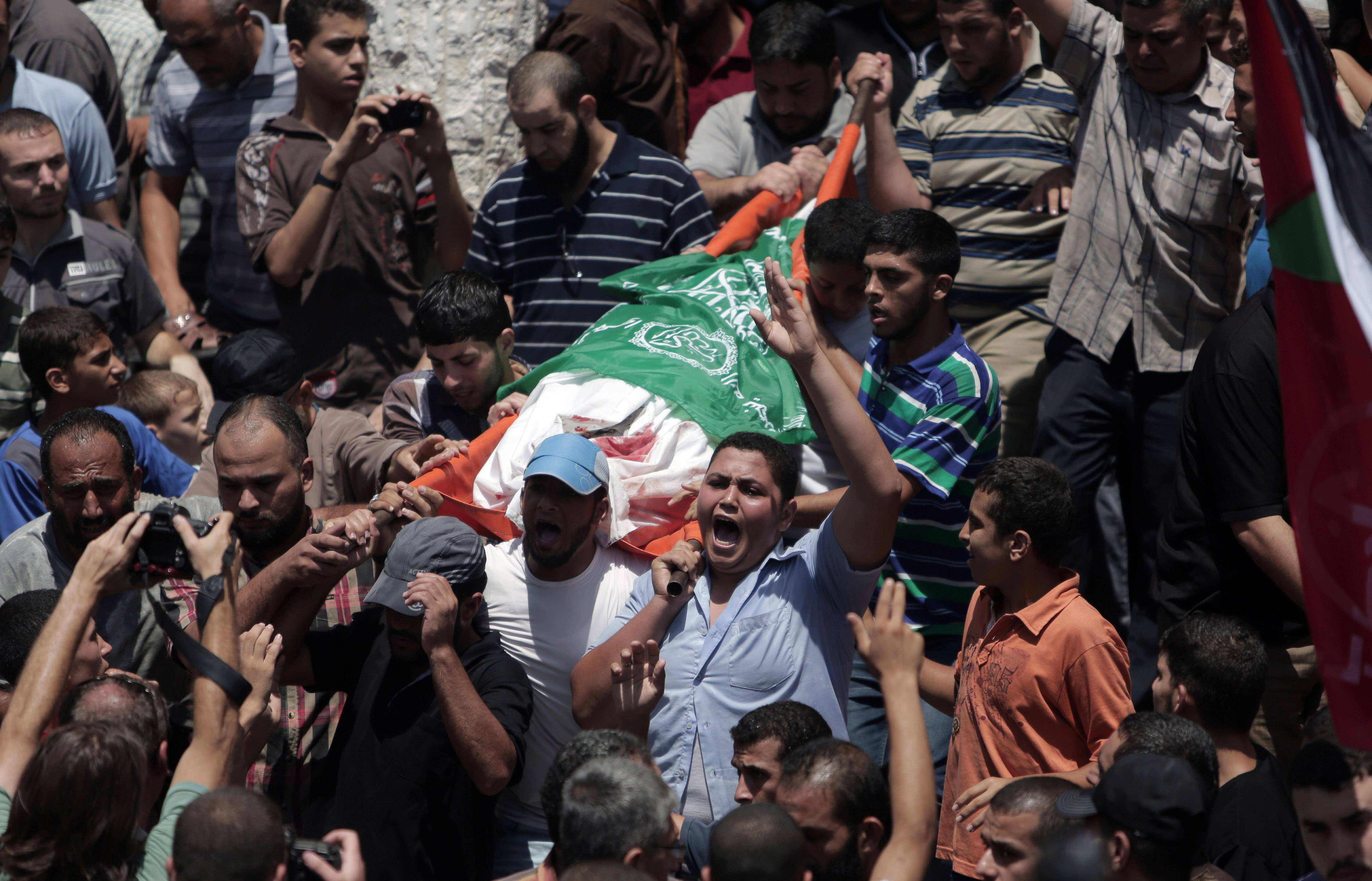 Mourners chant angry slogans Wednesday during the funeral of Widad Mustafa Deif, 27, who was killed along with her 8-month-old son in Israeli strikes in Gaza City late Tuesday. Widad was the wife of Mohammed Deif, the leader of the Hamas military wing.