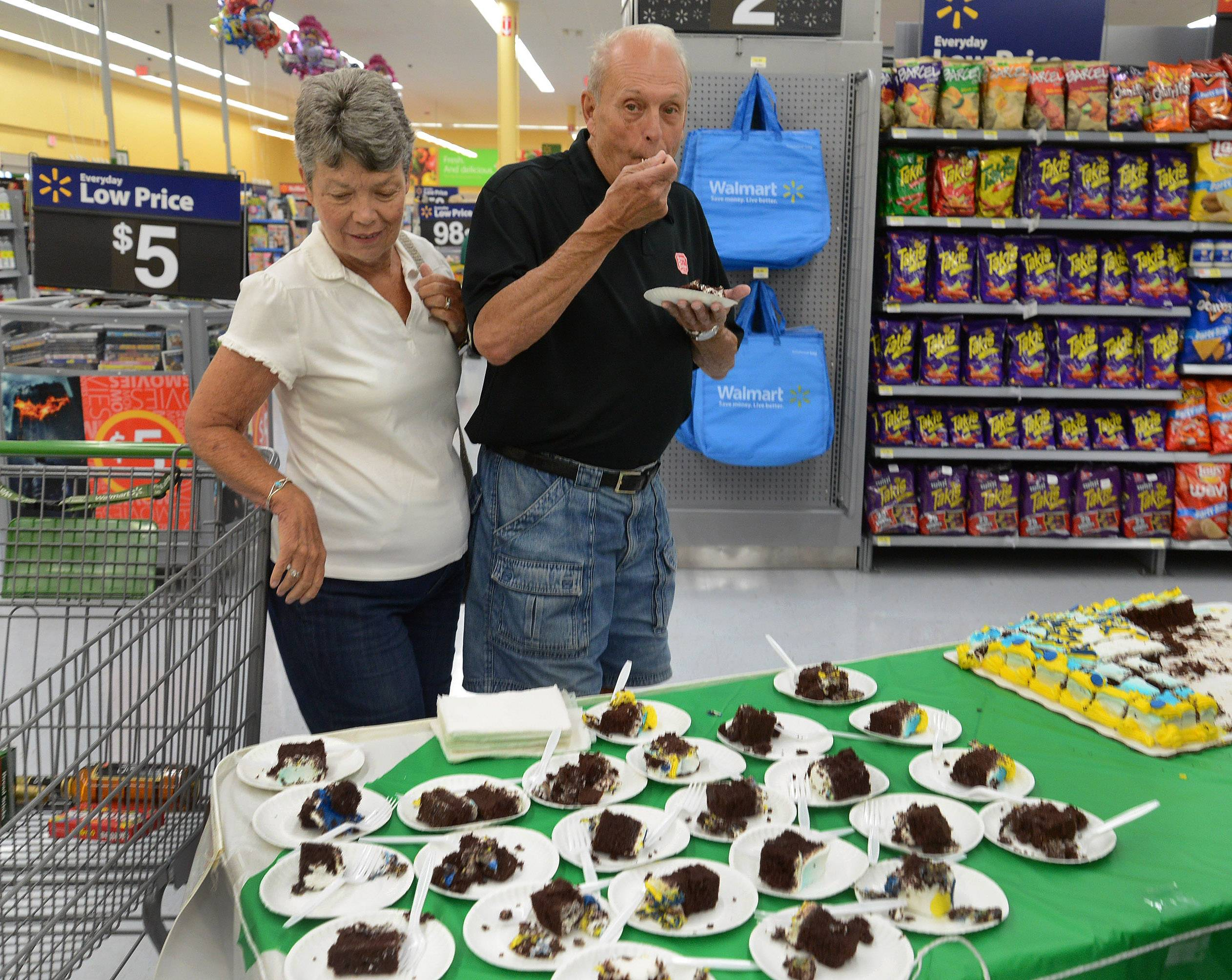 Judy and Carlton Hibbert of Des Plaines sample cake provided by the Dr Pepper Snapple Group during the grand opening of the Walmart Neighborhood Market in Des Plaines.