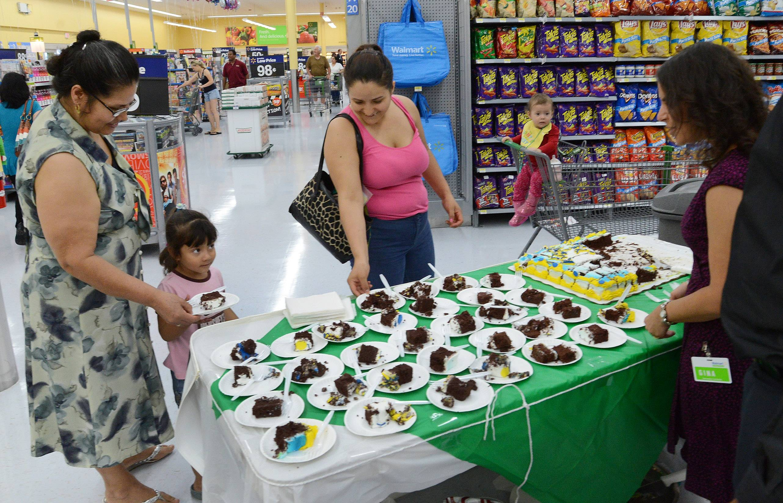 From left, Des Plaines residents Maria Casas, 4-year-old Dana Casas, Susana Casas and 1-year-old Martha Casas sample cake provided by Gina Thunstedt, far right, of the Dr Pepper Snapple Group, during the grand opening of the new Walmart Neighborhood Market in Des Plaines.