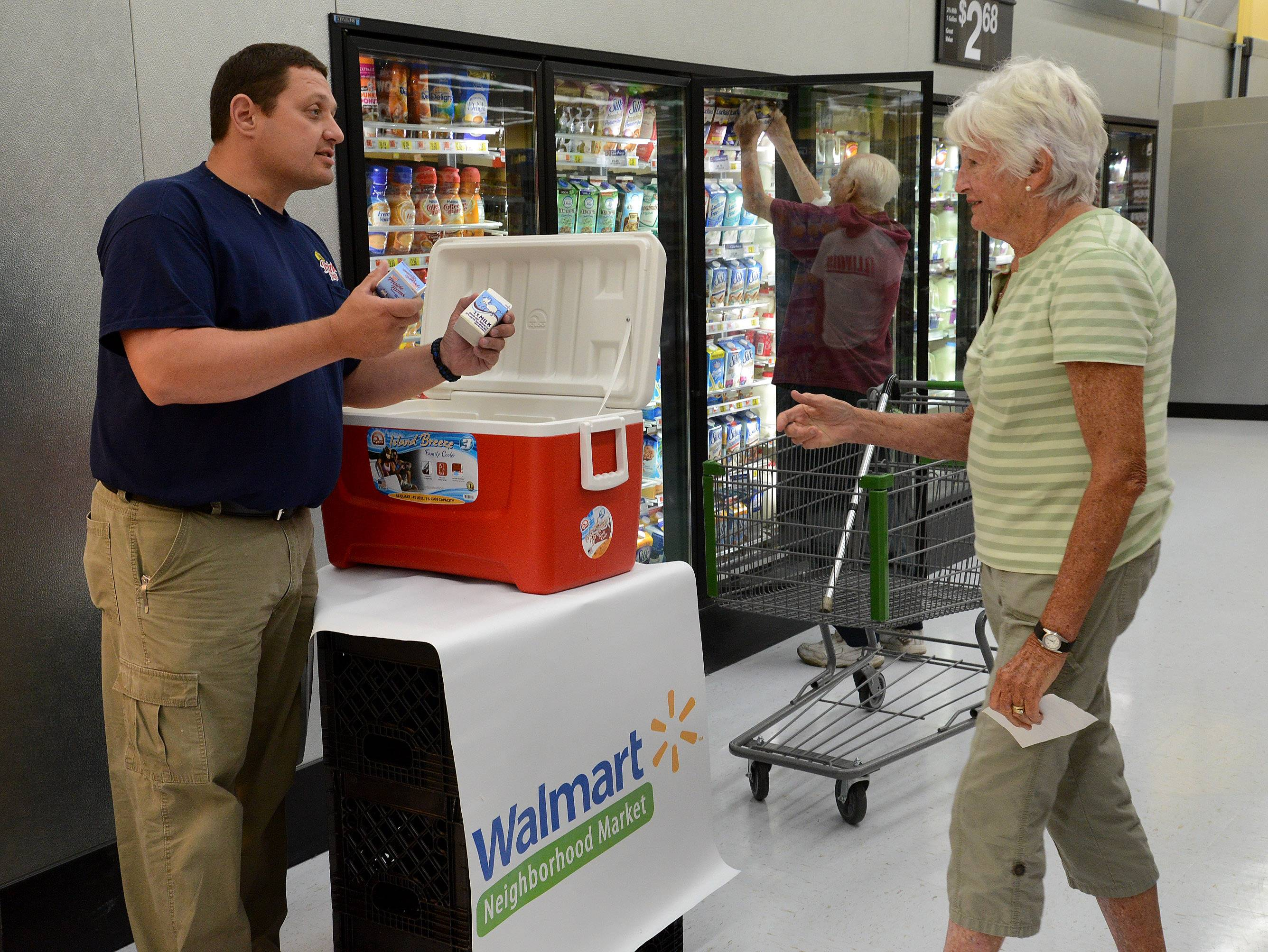 Dan Franks of Prairie Farms Dairy hands out free milk to Trish Brandenburg of Mount Prospect during the grand opening of the Walmart Neighborhood Market in Des Plaines.