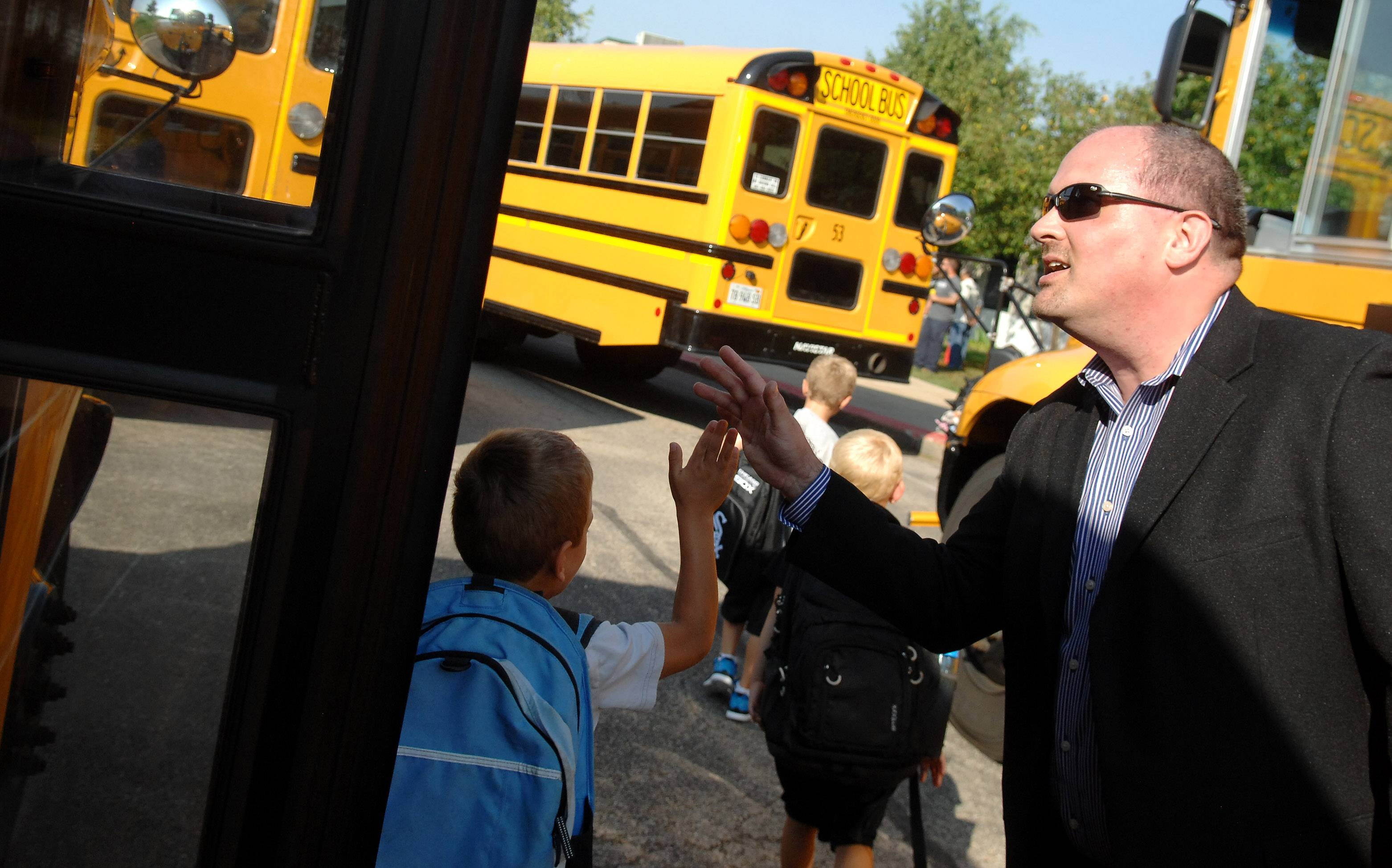 Principal Daniel Schuth high-fives kids as they get off the bus on the first day of classes Wednesday for Burlington Central District 301 students at Prairie View Grade School in Elgin.