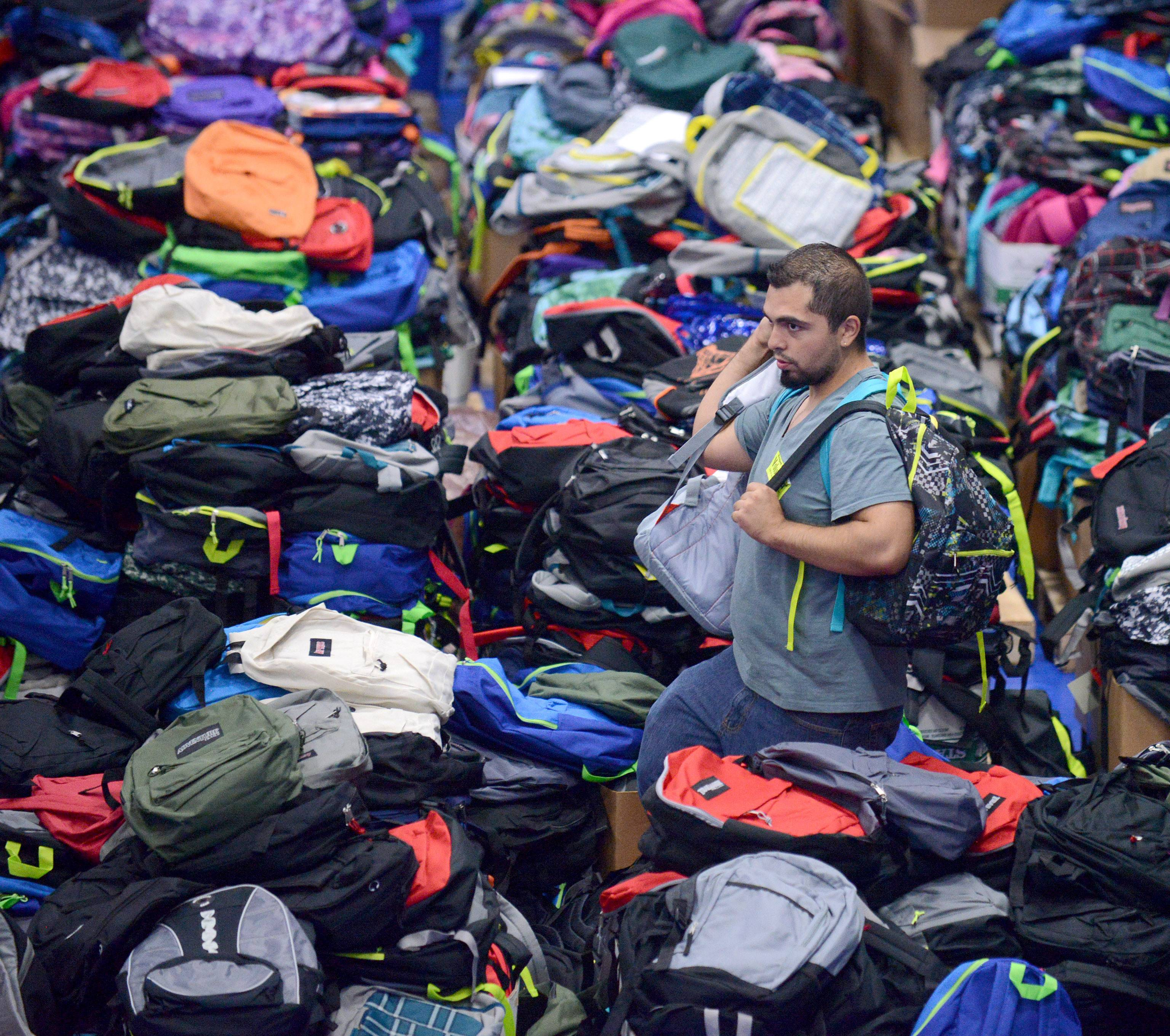Project Backpack volunteer and Elgin Community College alumni, Joel Aguilera of Elgin, grabs backpacks from the reserve piles to bring to students waiting in line to pick one out at a recent event. The free school supplies and backpacks were on a first-come, first-served basis to local students enrolled in schools.