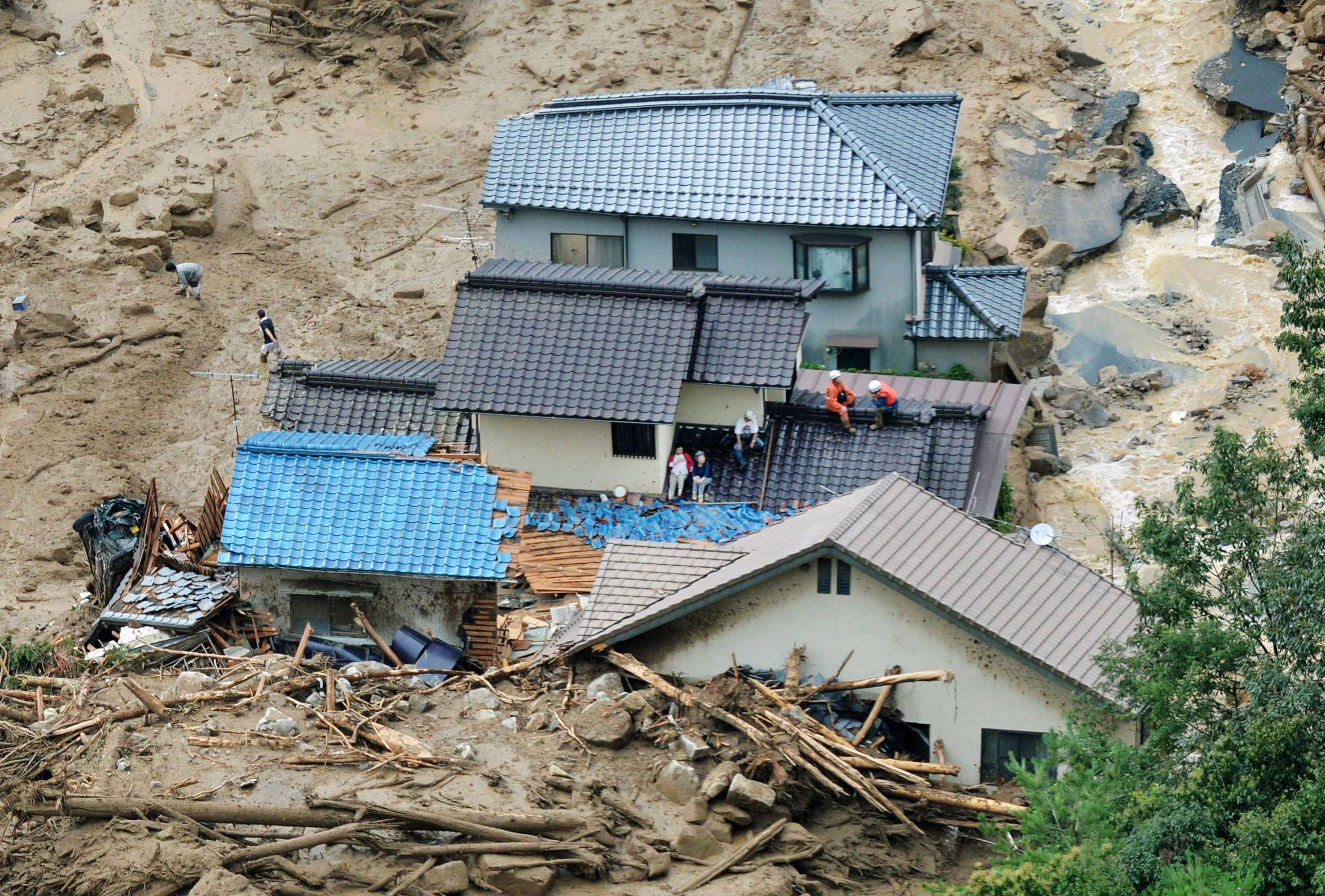 In this aerial photo, survivors and rescue workers sit on the roof of a damaged house after a massive landslide swept through residential areas in Hiroshima, western Japan, Wednesday, Aug. 20, 2014.