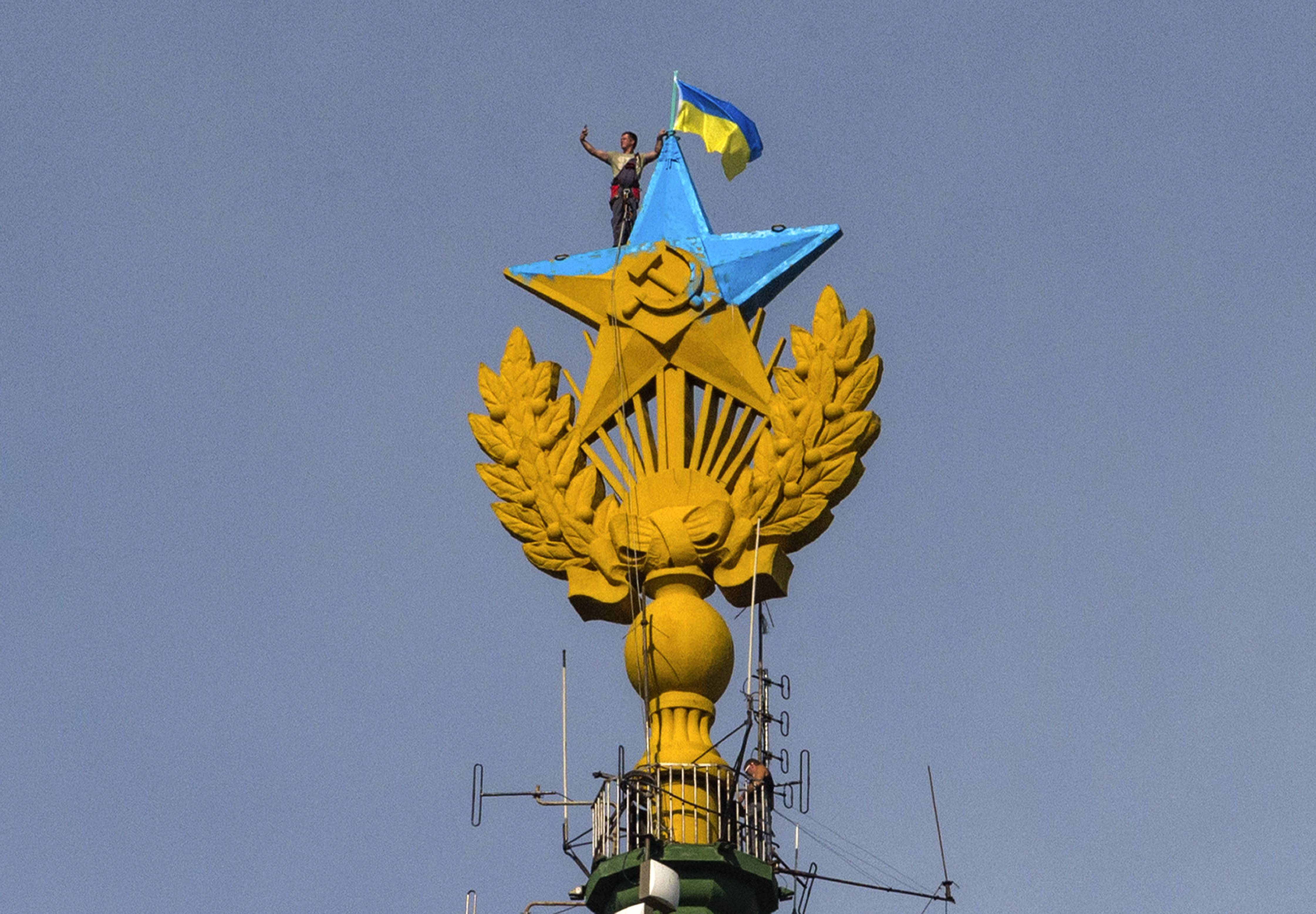 A worker takes a selfie before removing a yellow and blue Ukrainian flag attached by protesters atop Stalin-era skyscraper in Moscow, Russia.