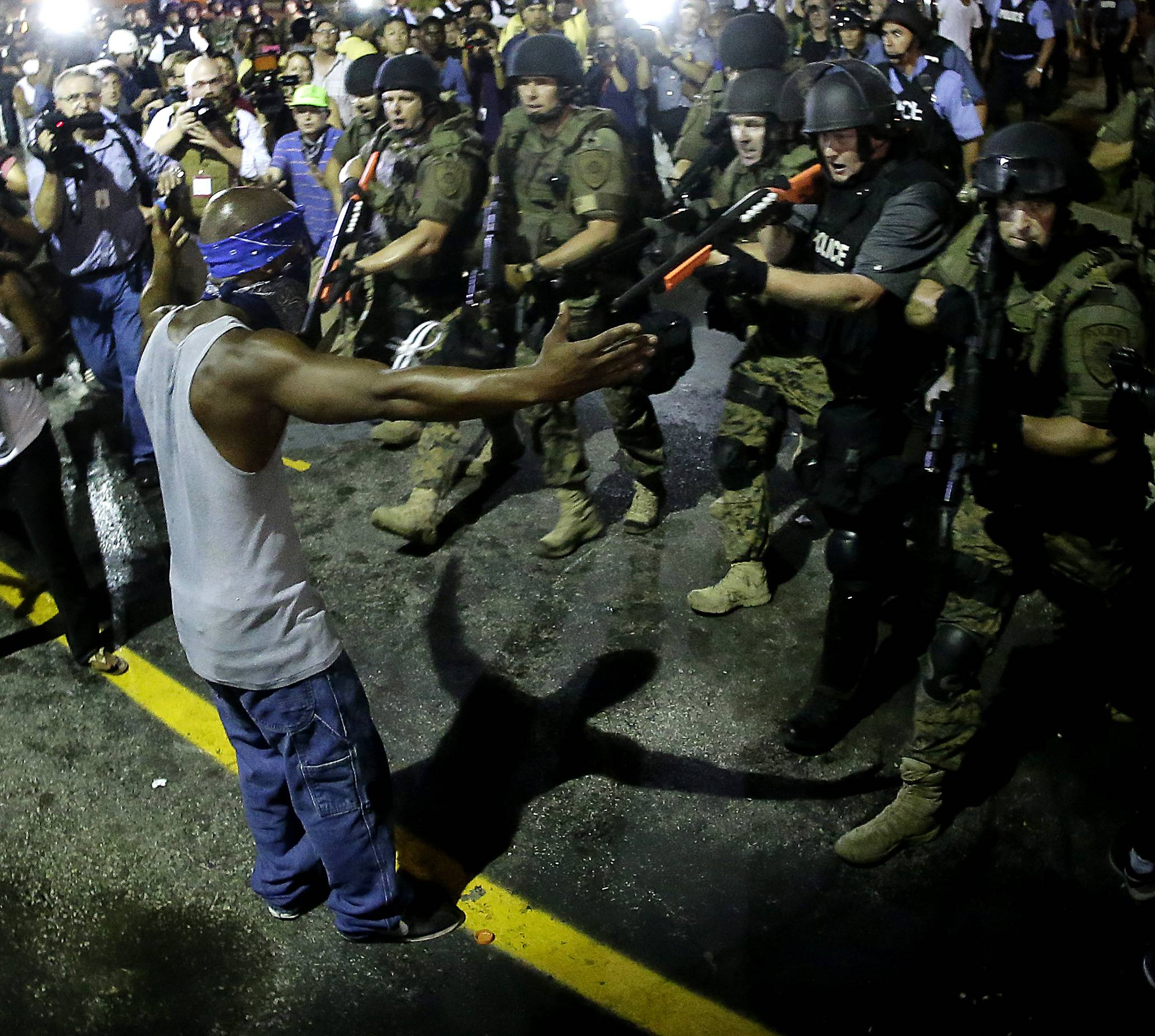 Police arrest a man as they disperse a protest in Ferguson, Mo., early Wednesday. On Saturday, a white police officer fatally shot Michael Brown, an unarmed black teenager, in the St. Louis suburb.