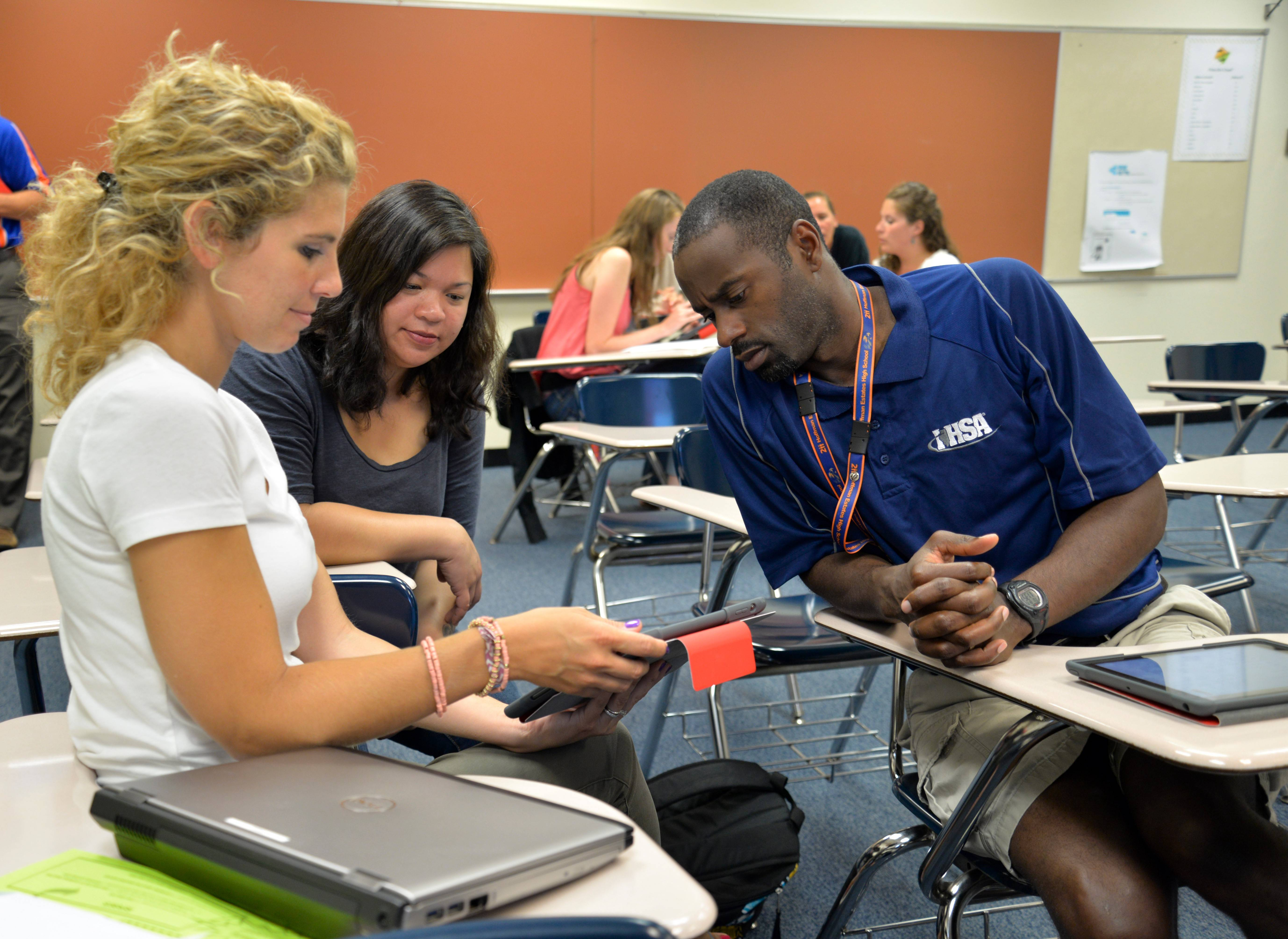 Hoffman Estates High School teachers, from left, Natalie Tindle, Jasmin Chung and Tyrone Jones collaborate Tuesday to learn new technology tools they can use during the school year.