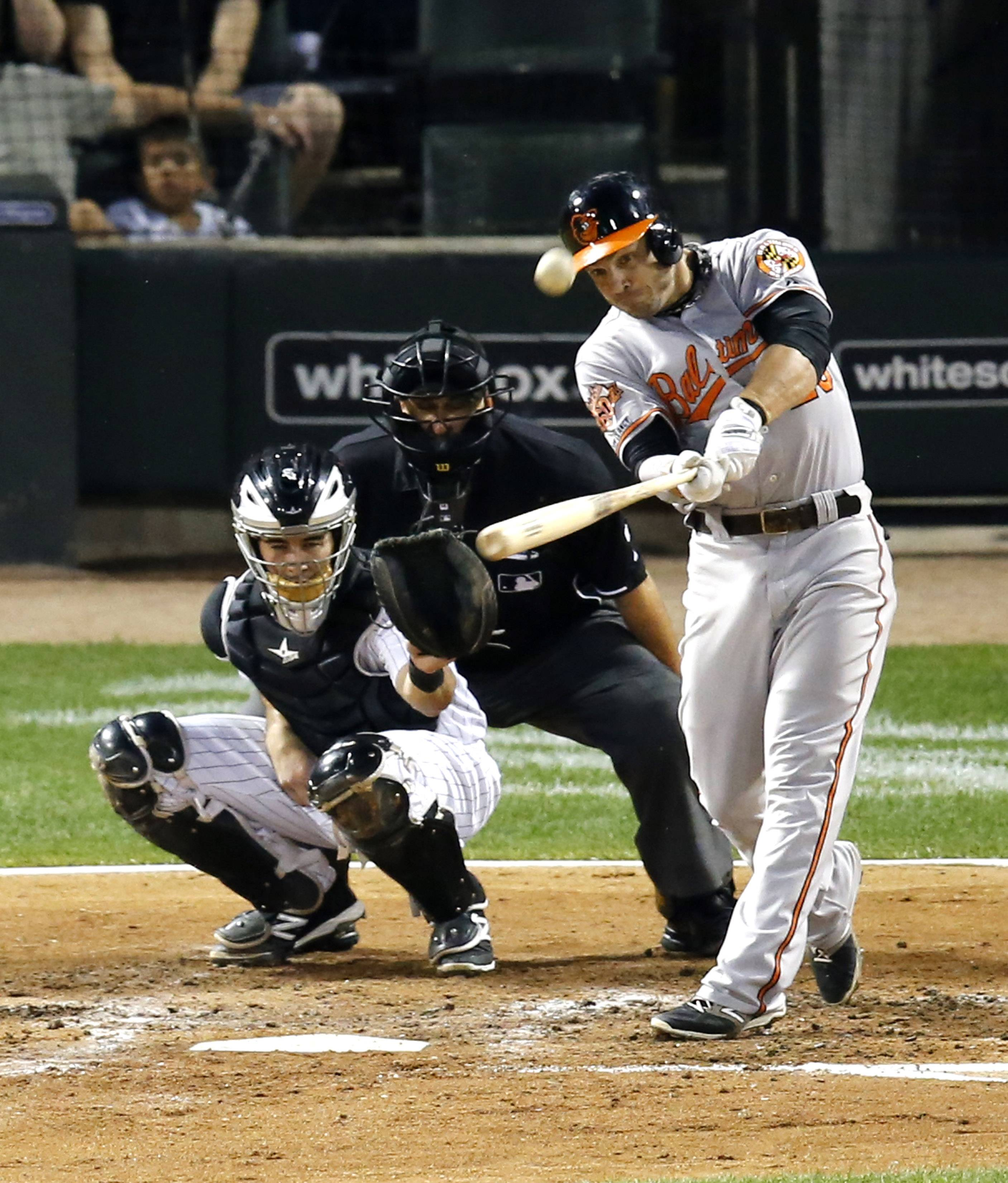 Baltimore Orioles' Steve Pearce hits a home run off Chicago White Sox starting pitcher Hector Noesi, during the fourth inning of a baseball game Wednesday, Aug. 20, 2014, in Chicago. Watching the play behind the plate are catcher Adrian Nieto and umpire Eric Cooper.