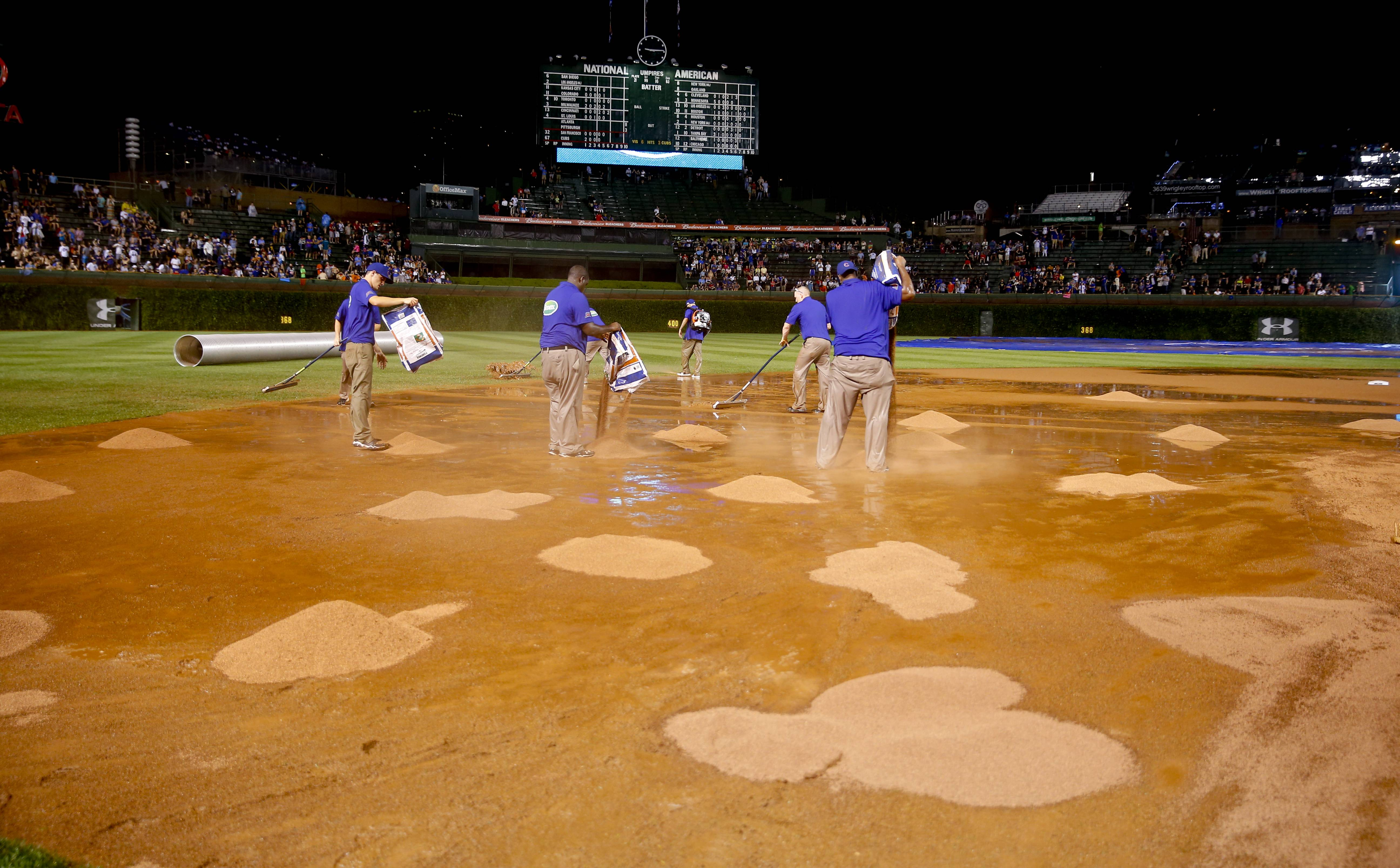 The grounds crew works on the field after a heavy rain soaked Wrigley Field during the fifth inning of a baseball game Tuesday between the San Francisco Giants and the Chicago Cubs in Chicago.