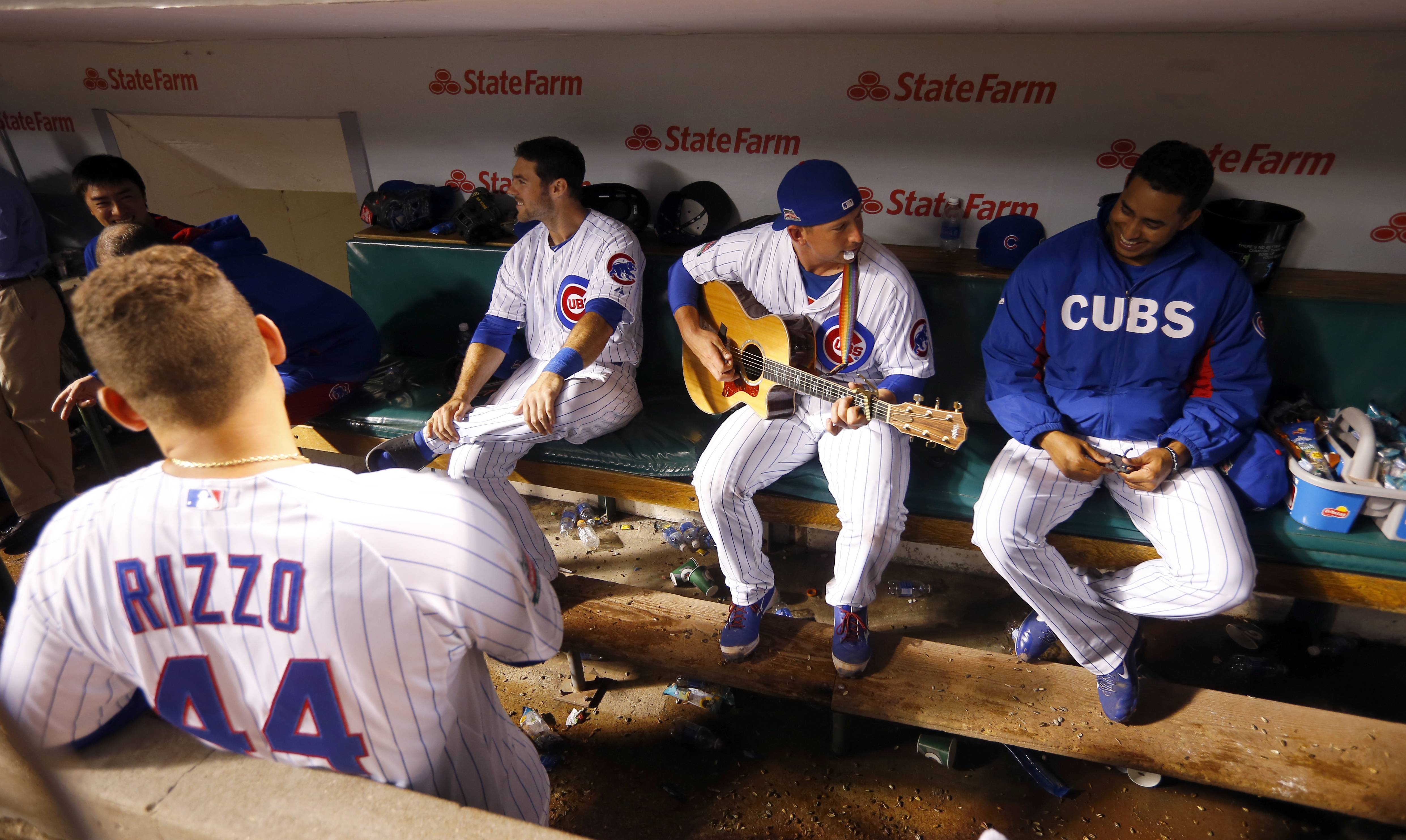 Chicago Cub backup catcher John Baker, center, plays his guitar during a rain delay at Wrigley Field during the fifth inning of a baseball game between the San Francisco Giants and the Chicago Cubs on Tuesday in Chicago.