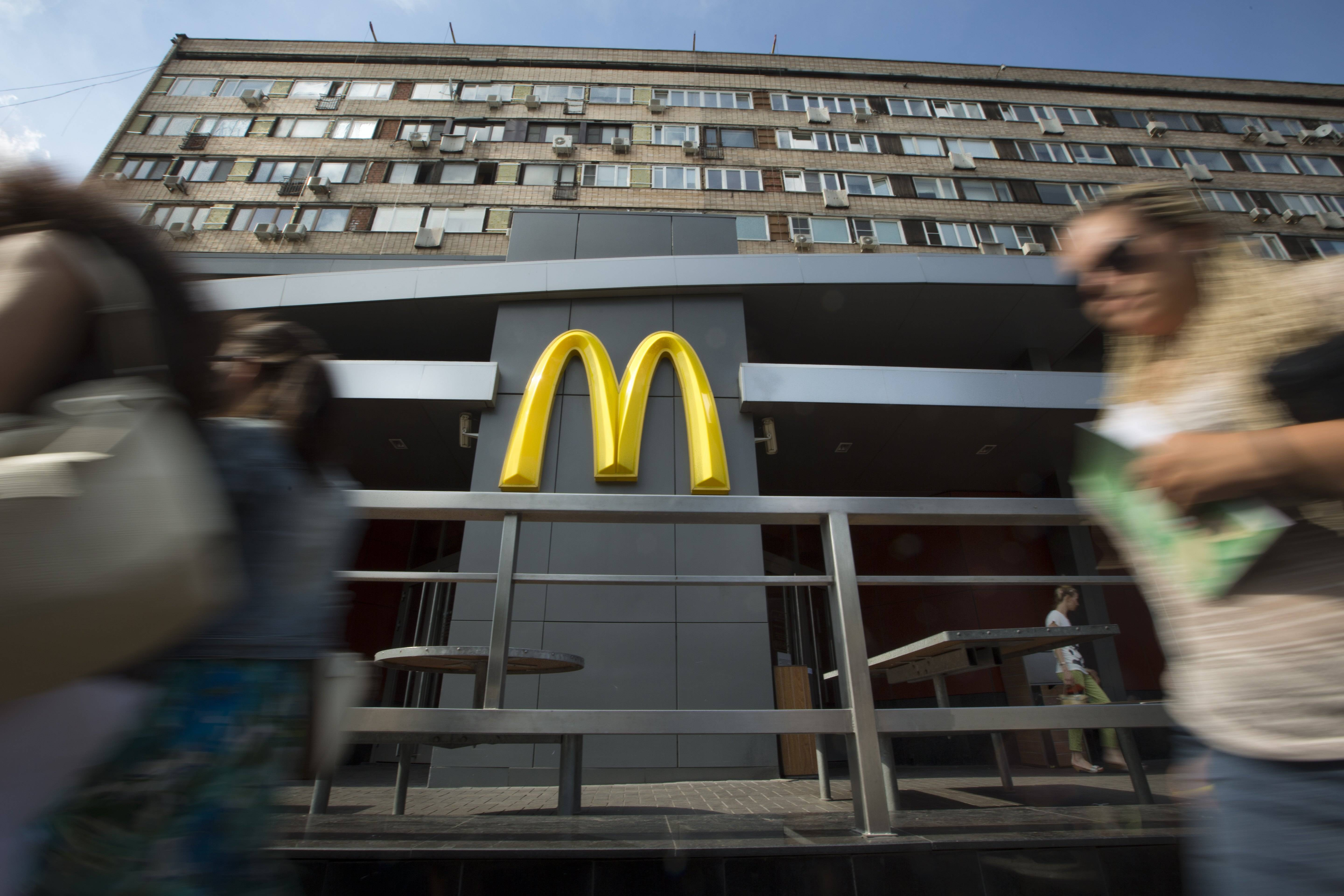 People walk past the oldest of Moscow's McDonald's outlets which was opened on Jan. 31, 1990, and closed on Thursday, Aug. 21, 2014.