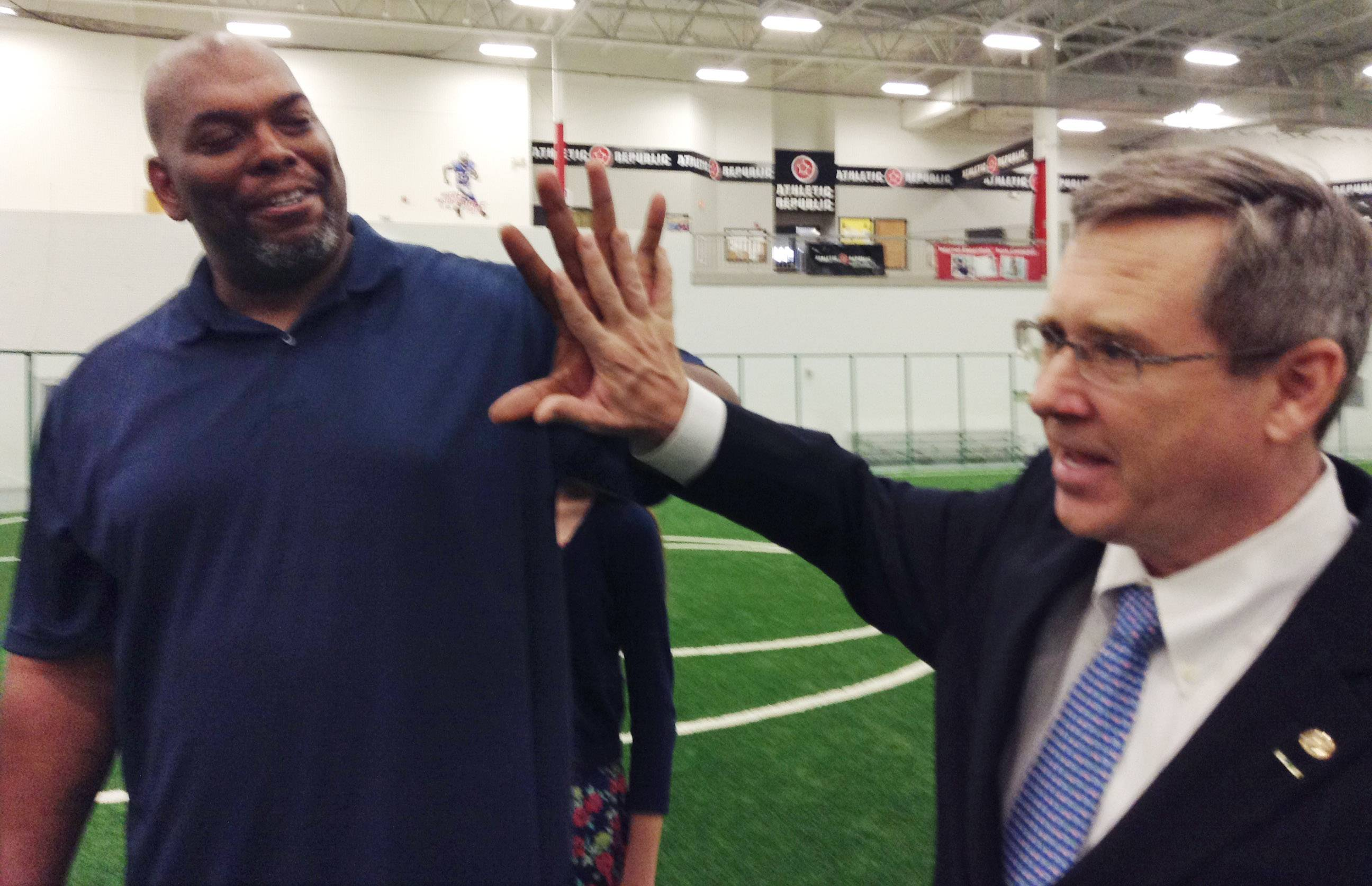 "Former Bears lineman James ""Big Cat"" Williams, left, and Sen. Mark Kirk compare hand sizes Thursday in Libertyville during the recording of a public service announcement about cyberbullying."