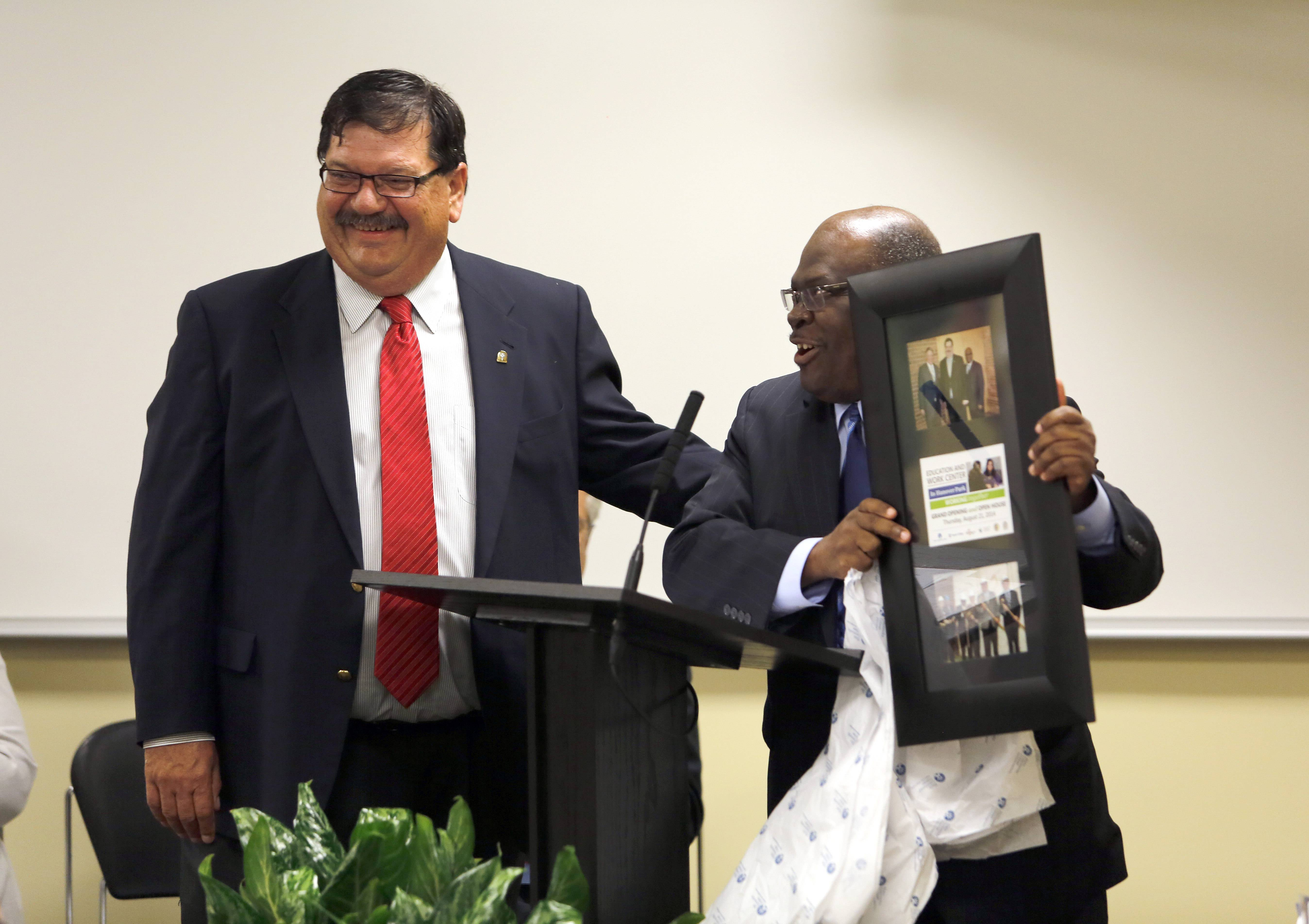 Hanover Park Mayor Rodney Craig receives a gift from Elgin Community College President David Sam during the opening of the Education and Work Center Thursday.