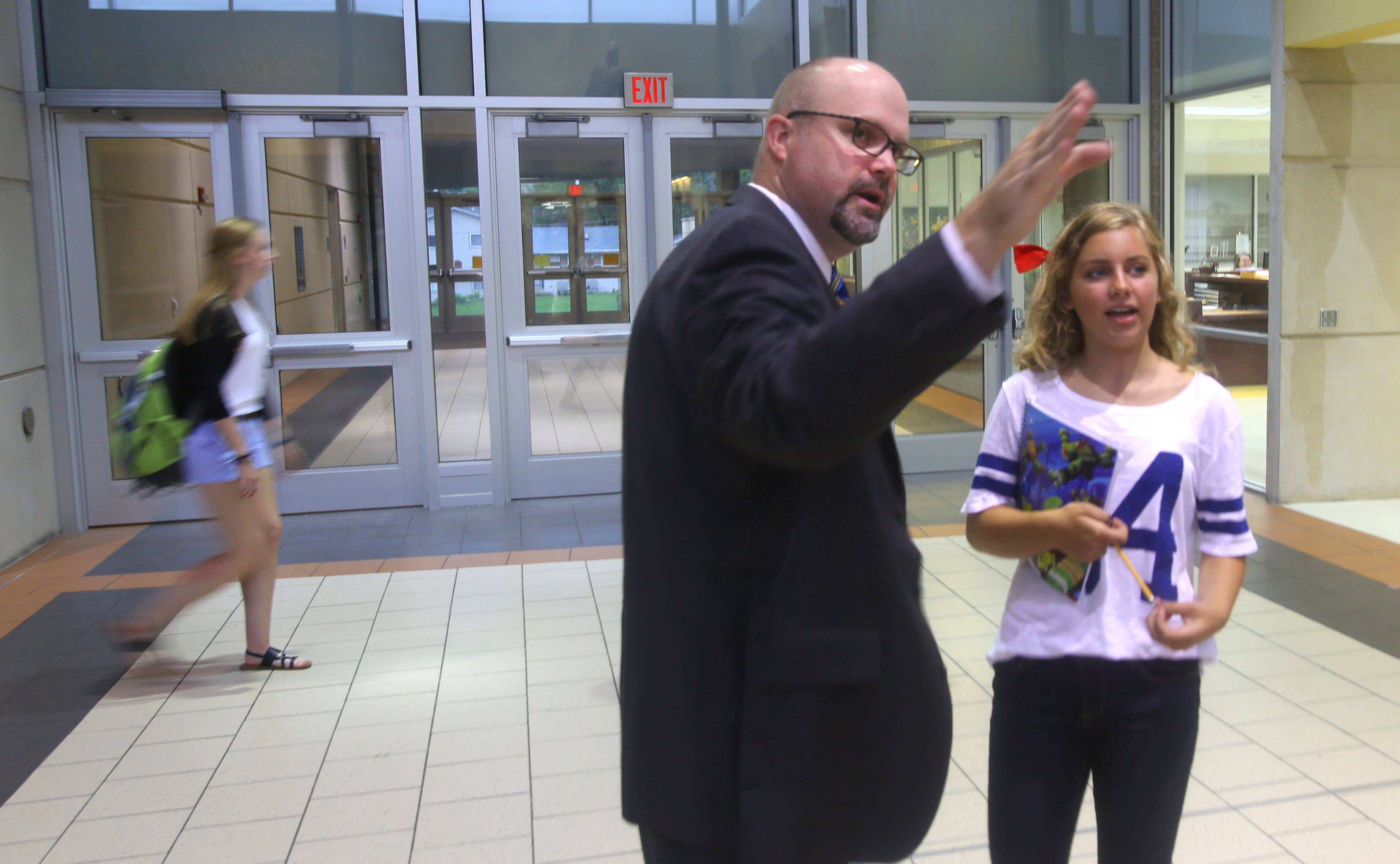 Wheaton North High School Principal Matt Biscan gets freshman Cara Parker headed in the right direction during the first day of classes Thursday.