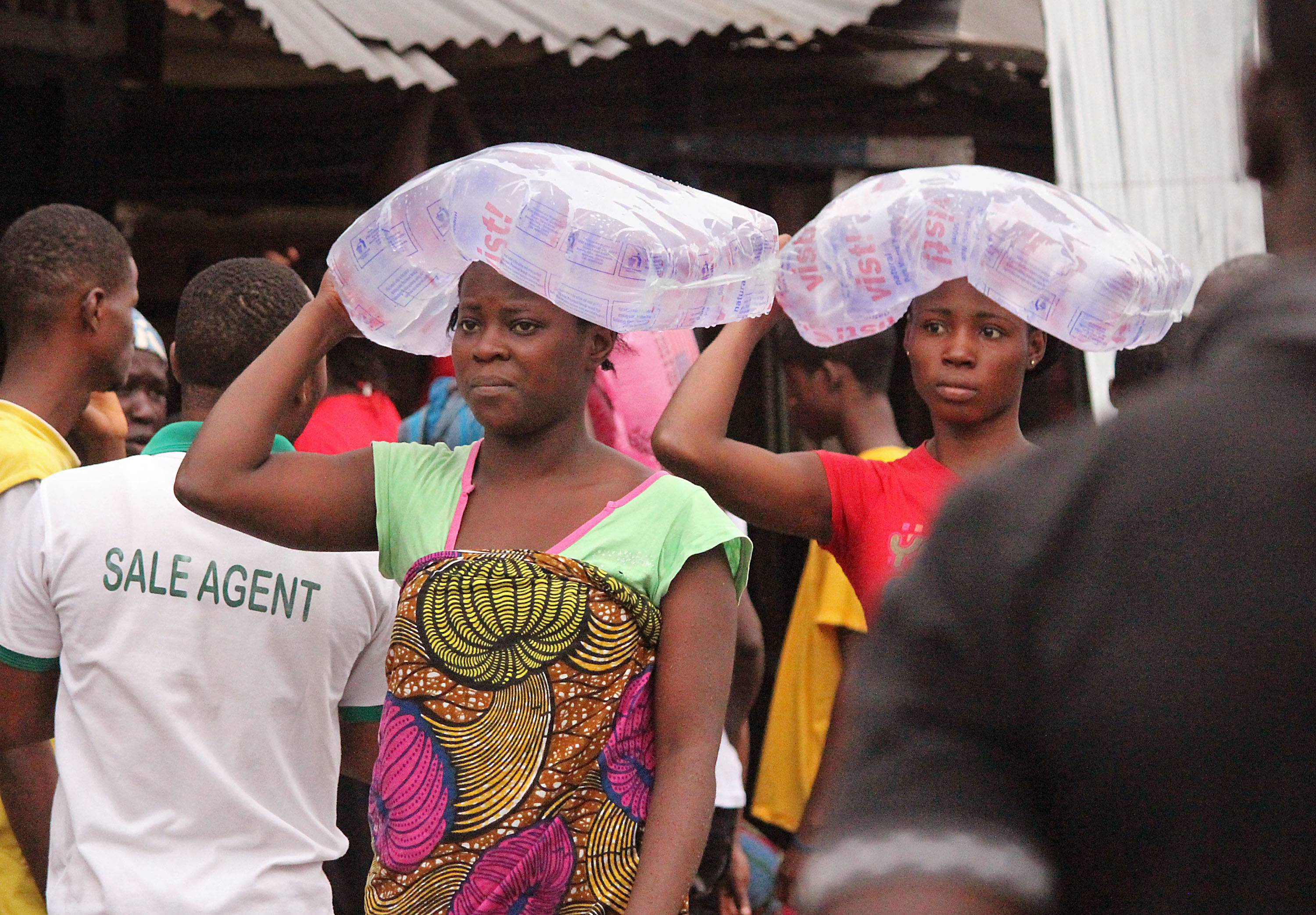 Woman from West Point carry water on their heads as they sell water to fellow residents in one of the areas where the Ebola virus has claimed lives in Monrovia, Liberia, Thursday.