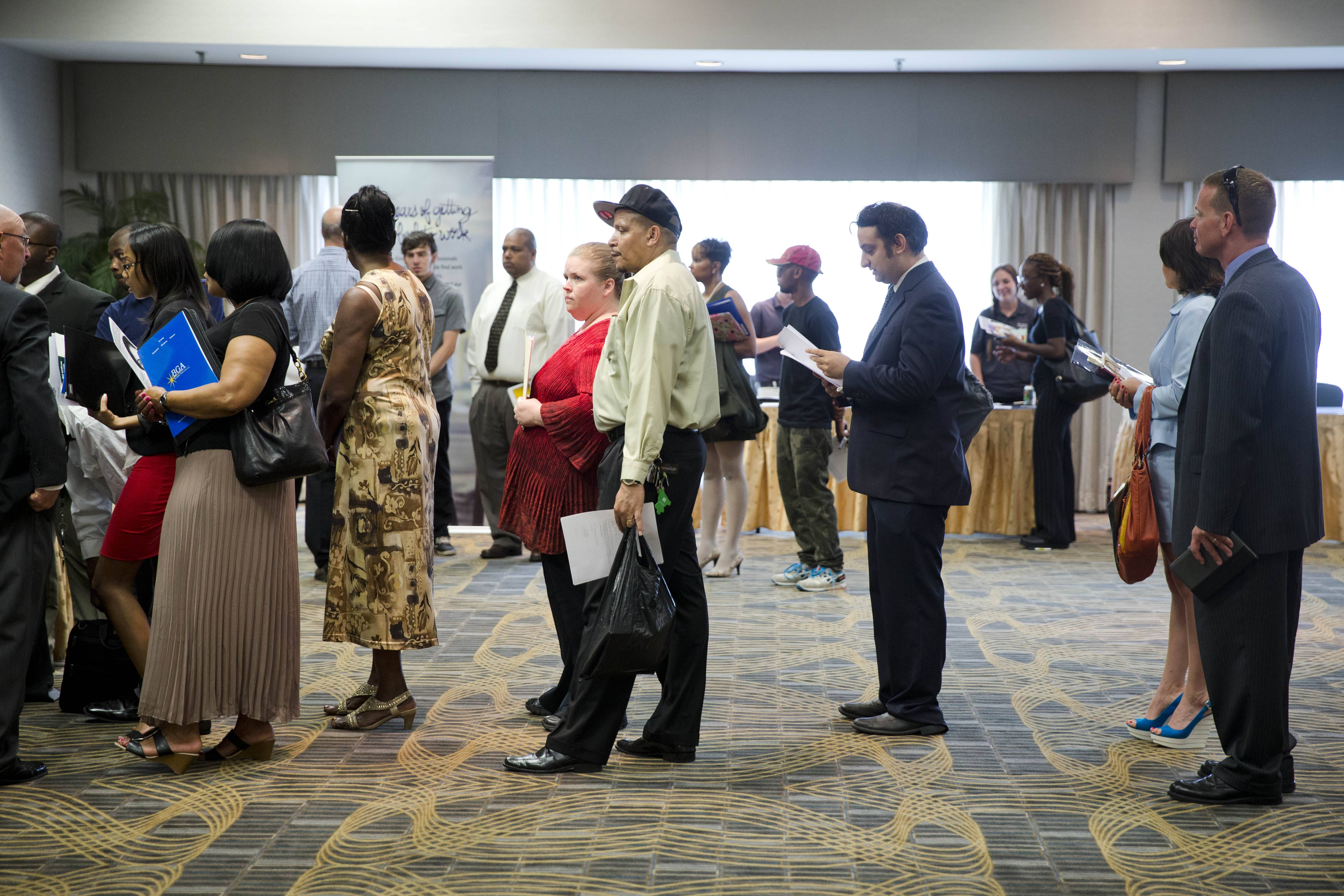 People wait in line to meet with recruiters during a job fair in Philadelphia. Fewer people applied for U.S. unemployment benefits last week, another sign the job market is improving.