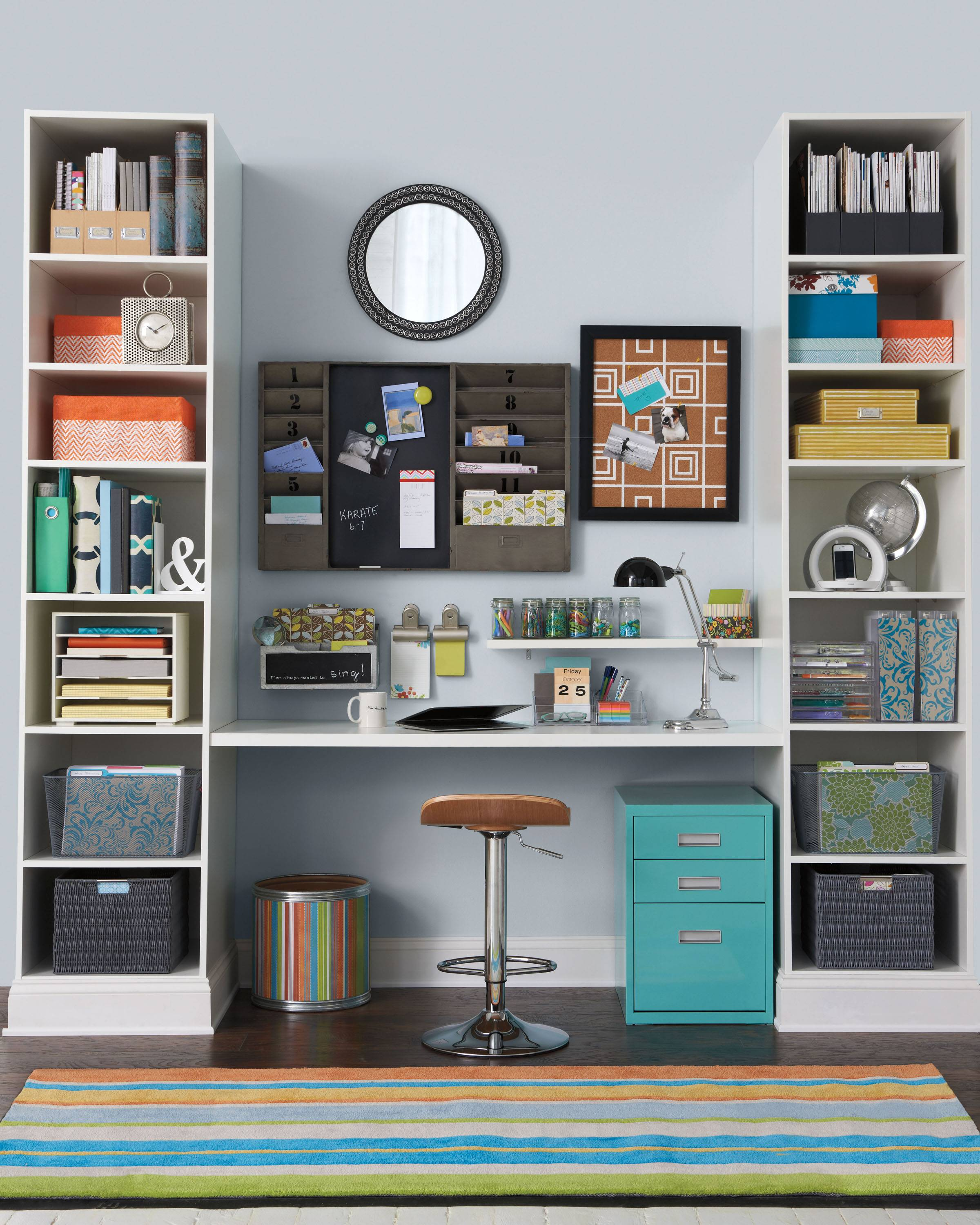 A teal blue file cabinet and striped rug add extra pops of color to a plain white room. This work space is organized with baskets and bins.