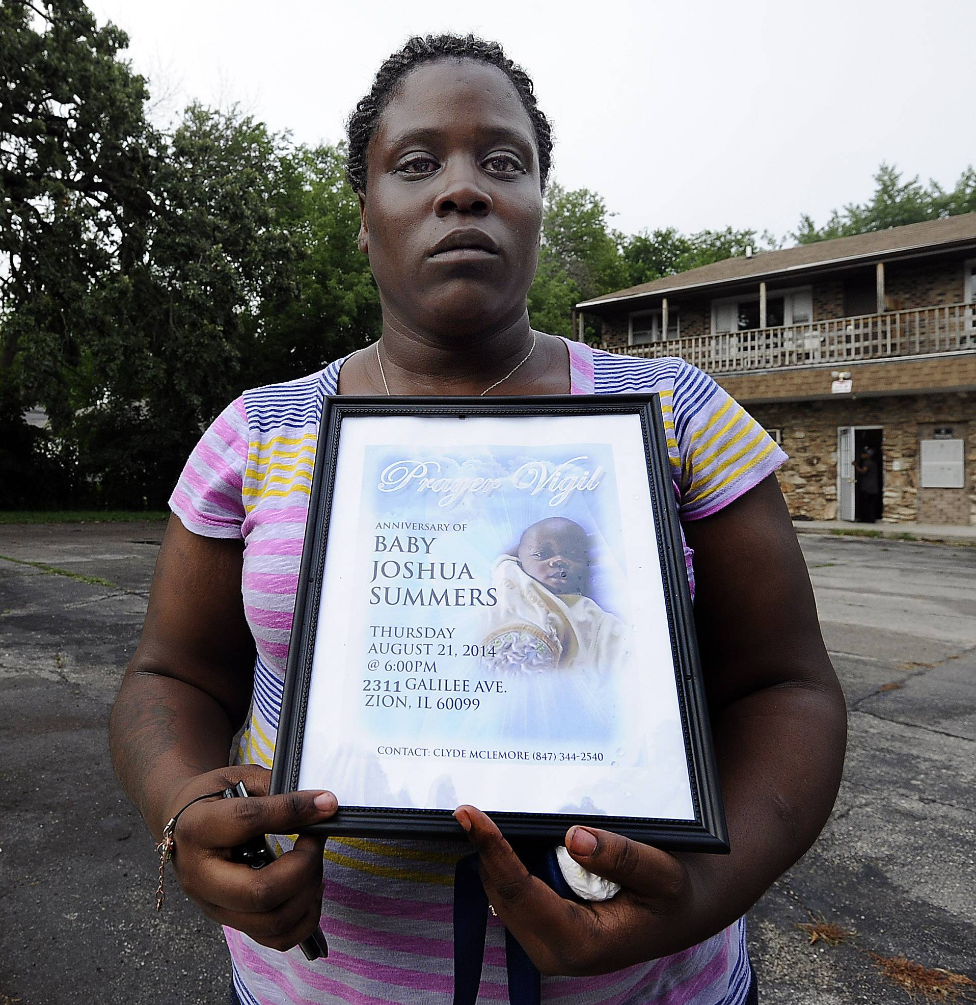 Kisha Summeries, mother of baby Joshua. holds a picture marking the anniversary of her son's death in Zion at a prayer service held in his honor Thursday.