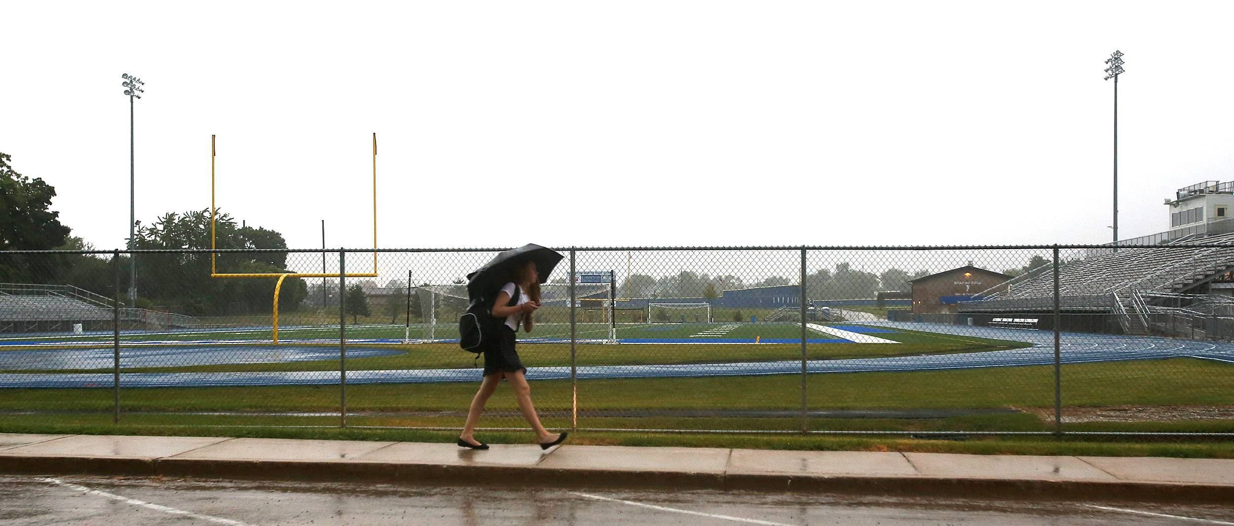 Students battle a morning rain Thursday during the first day of classes at Wheaton North High School. A new track installed this summer circles the school's football field.