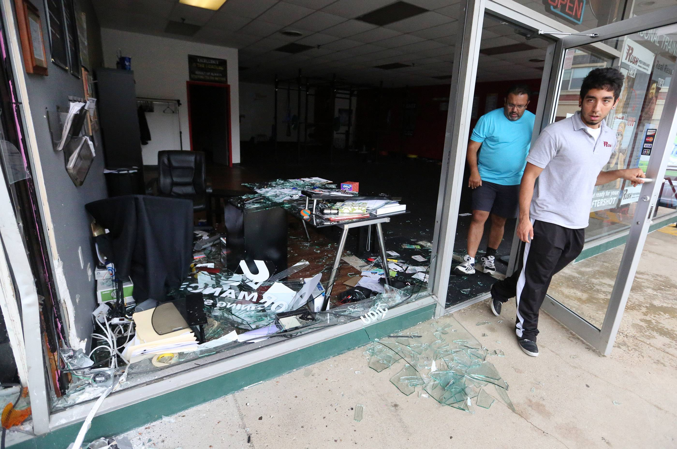 A.J. Rivera, general manager of Rush Performance personal training studio in Arlington Heights, leaves his business Thursday after evaluating damages caused by an SUV that crashed.