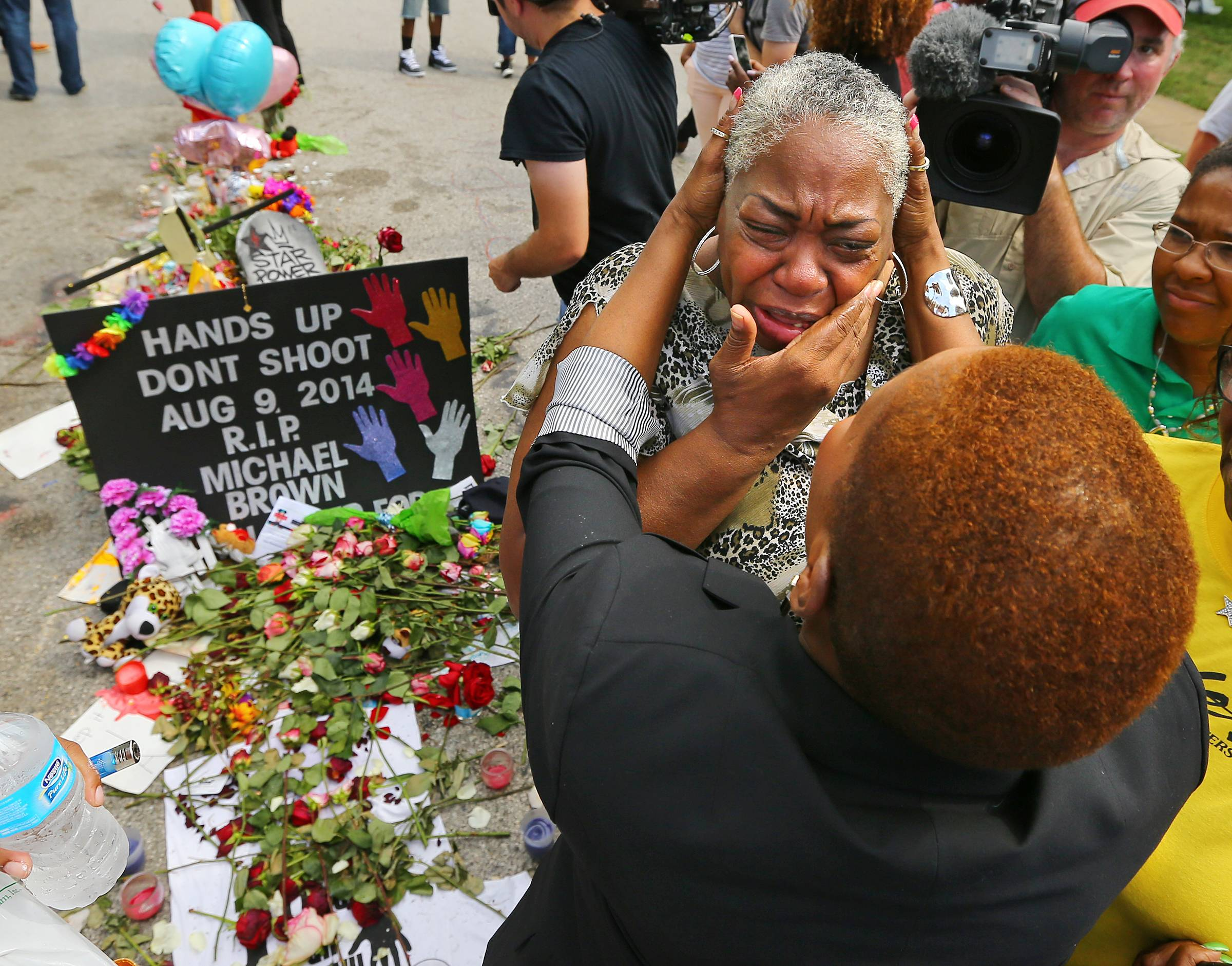 Iyanla Vanzant, right, consoles Shirley Scale, a resident at the Canfield Apartments, at the shrine to Michael Brown where he was shot and killed on Wednesday, Aug. 20, 2014, in Ferguson, Mo.