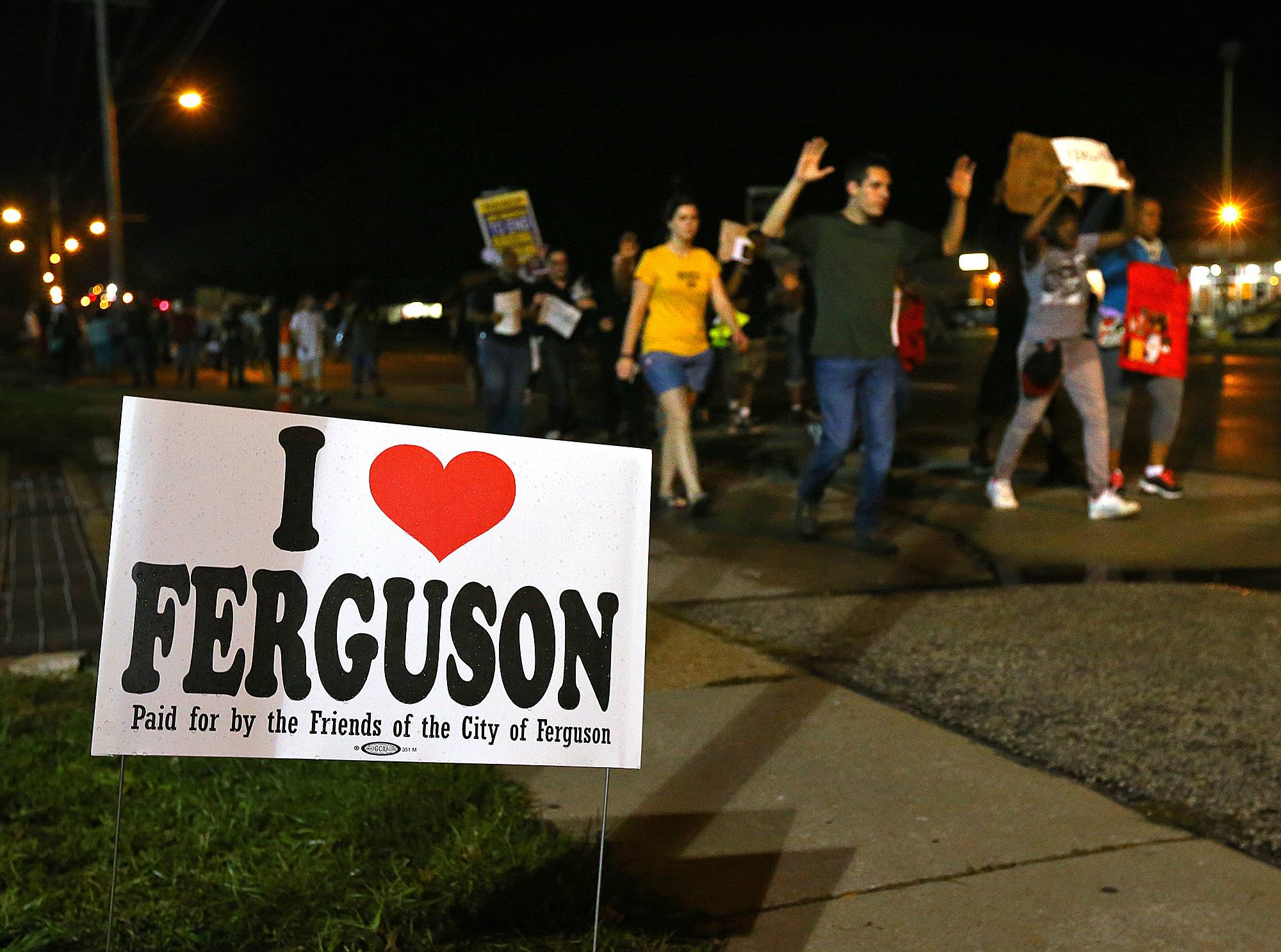 A small group of protesters marches down West Florissant Avenue in Ferguson, Mo. on Wednesday, Aug. 20, 2014. On Aug. 9, 2014, a white police officer fatally shot Michael Brown, an unarmed black 18-year old, in the St. Louis suburb.