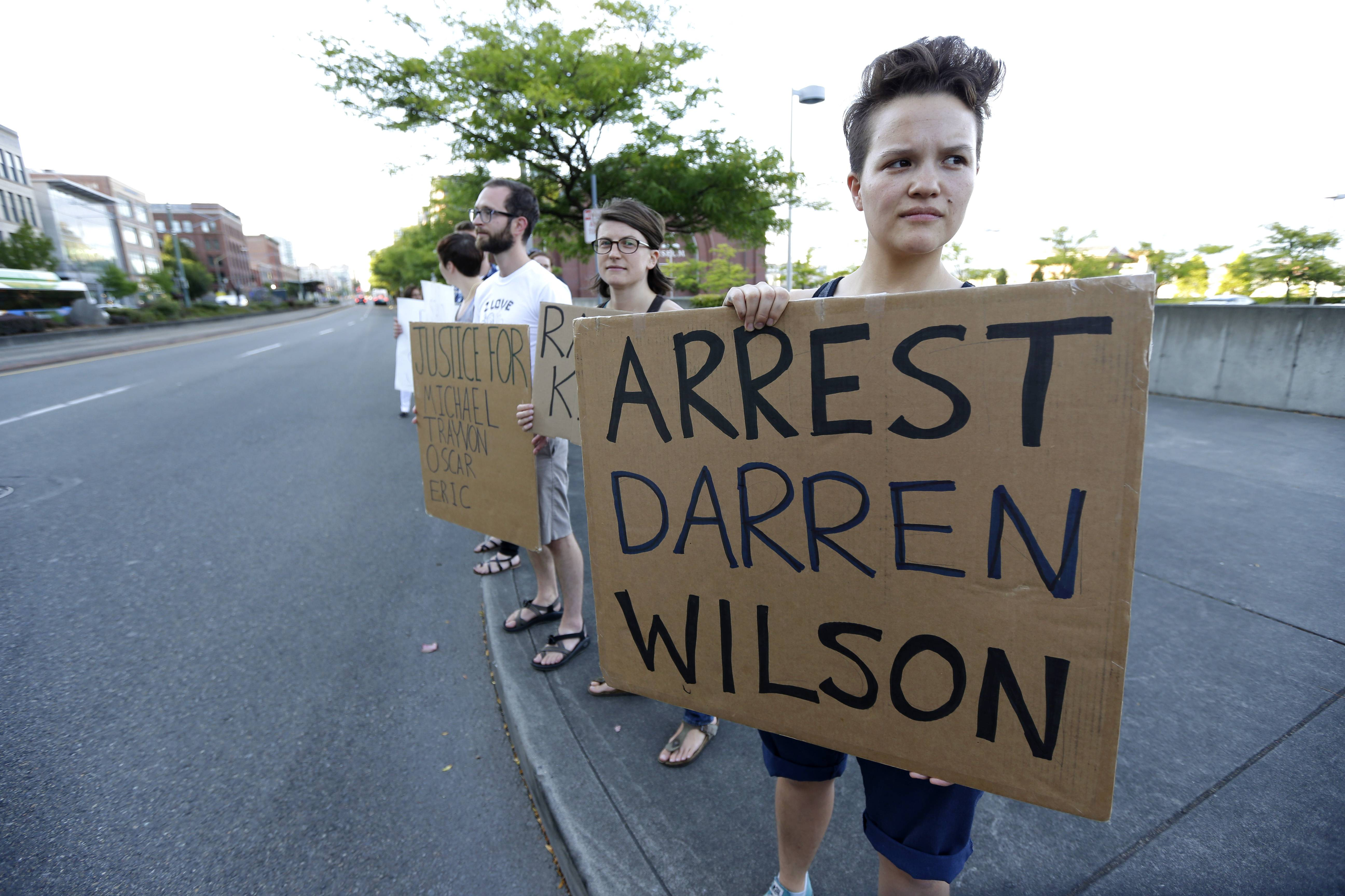 "Protester Hana Kato, of Tacoma, Wash., holds a sign that reads ""Arrest Darren Wilson"" as she attends an evening rally Tuesday, Aug. 19, 2014, in Tacoma, Wash. Wilson has been identified as the police officer who fatally shot 18-year-old Michael Brown in Ferguson, Missouri, an event that has sparked nightly clashes between protesters and police."