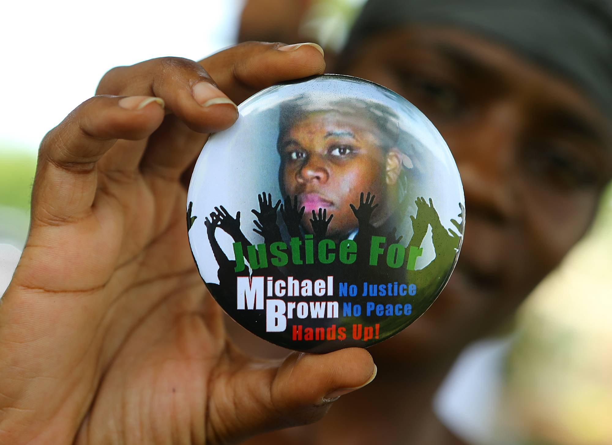 Nikki Jones, of Spanish Lake, Mo., holds a button Thursday in support of Michael Brown while visiting near where he was fatally shot by police in Ferguson, Mo.