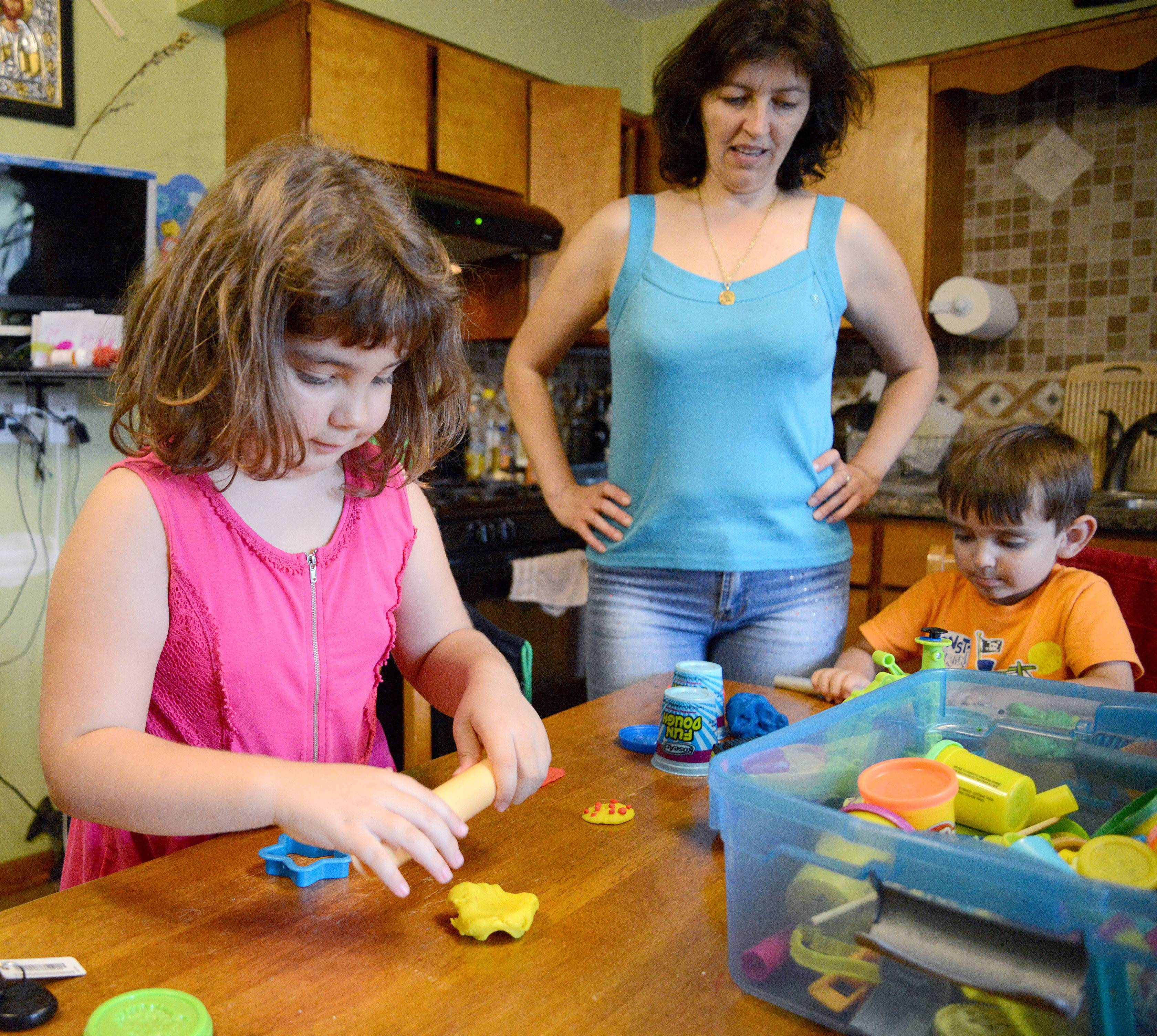Elena Serban watches her children, Maria and Victor, play with Play-Doh at the kitchen table in their South Elgin home. Maria has juvenile idiopathic arthritis.
