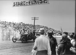 The Elgin Road Races began a year before racing in Indianapolis and attracted the world's best drivers and cars to the city. Autos are shown lining up for an early race at the starting line located near the current Larkin High School.