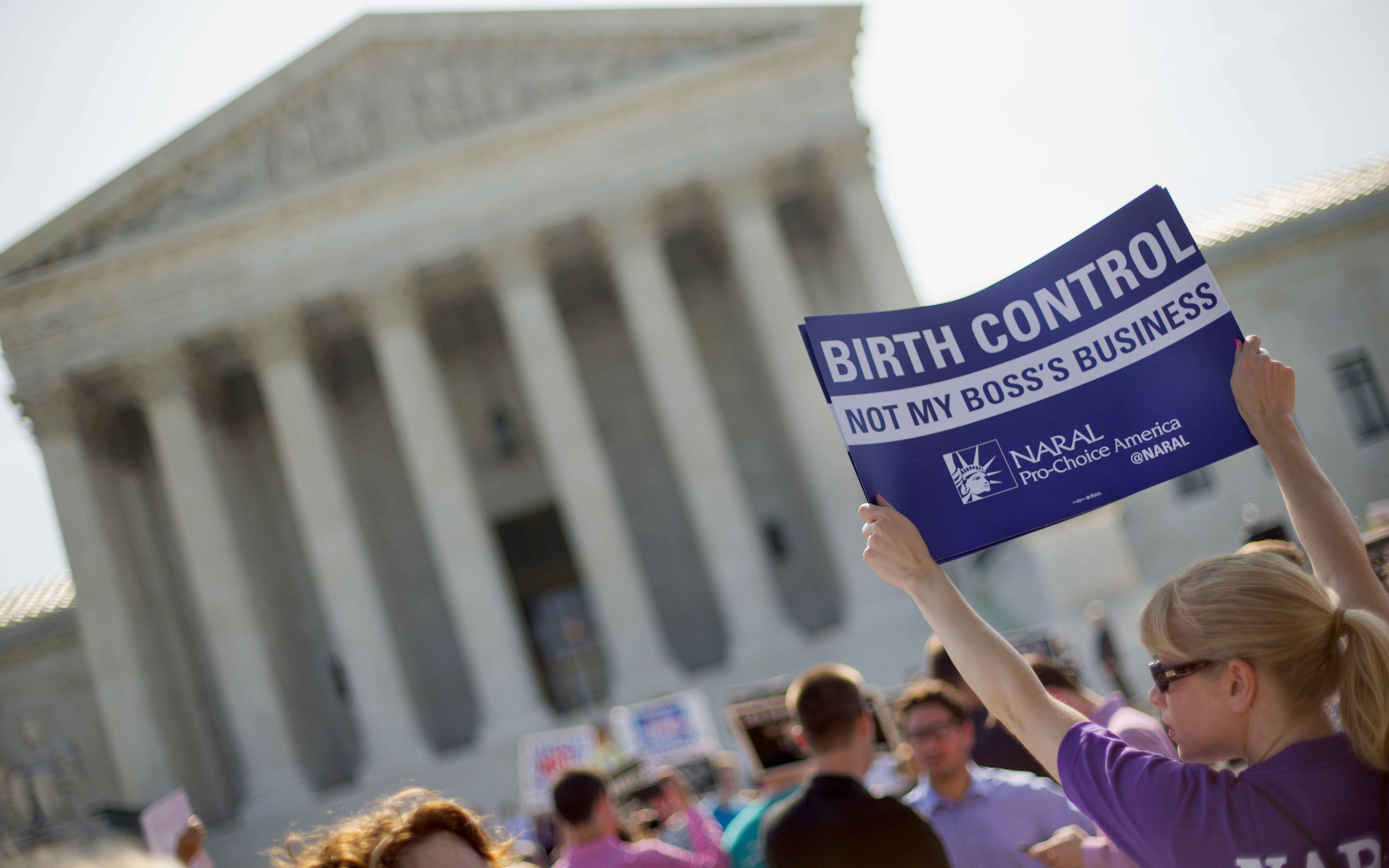 A demonstrator holding up a sign outside the Supreme Court in Washington. Seeking to quell a politically charged controversy, the Obama administration announced new measures Friday to allow religious nonprofits and some companies to opt out of paying for birth control for female employees.