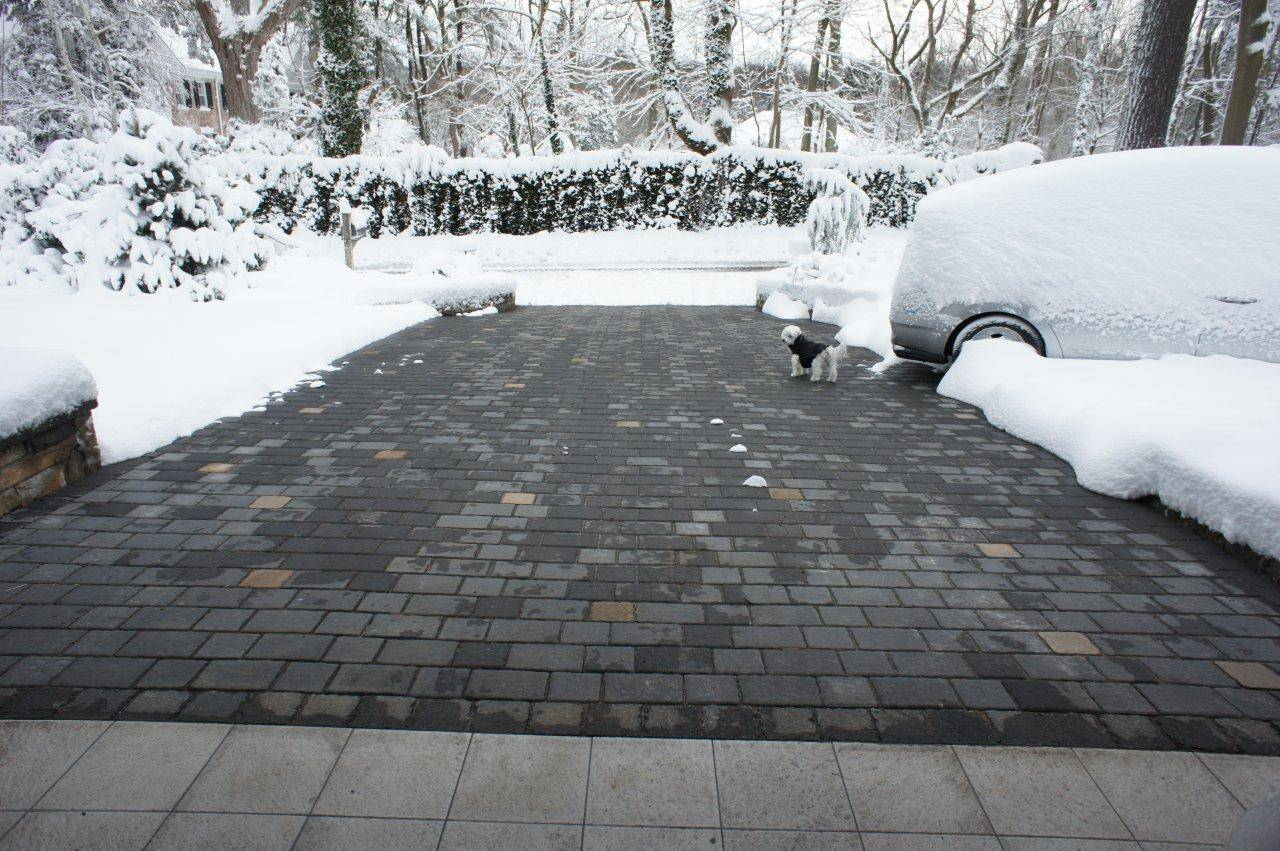 Warmzone, a Utah-based radiant heating company, shows how it installs a heating system, left, under a driveway before paving stones are put in place. At right, one of its heated driveways remains clear after a big snow.