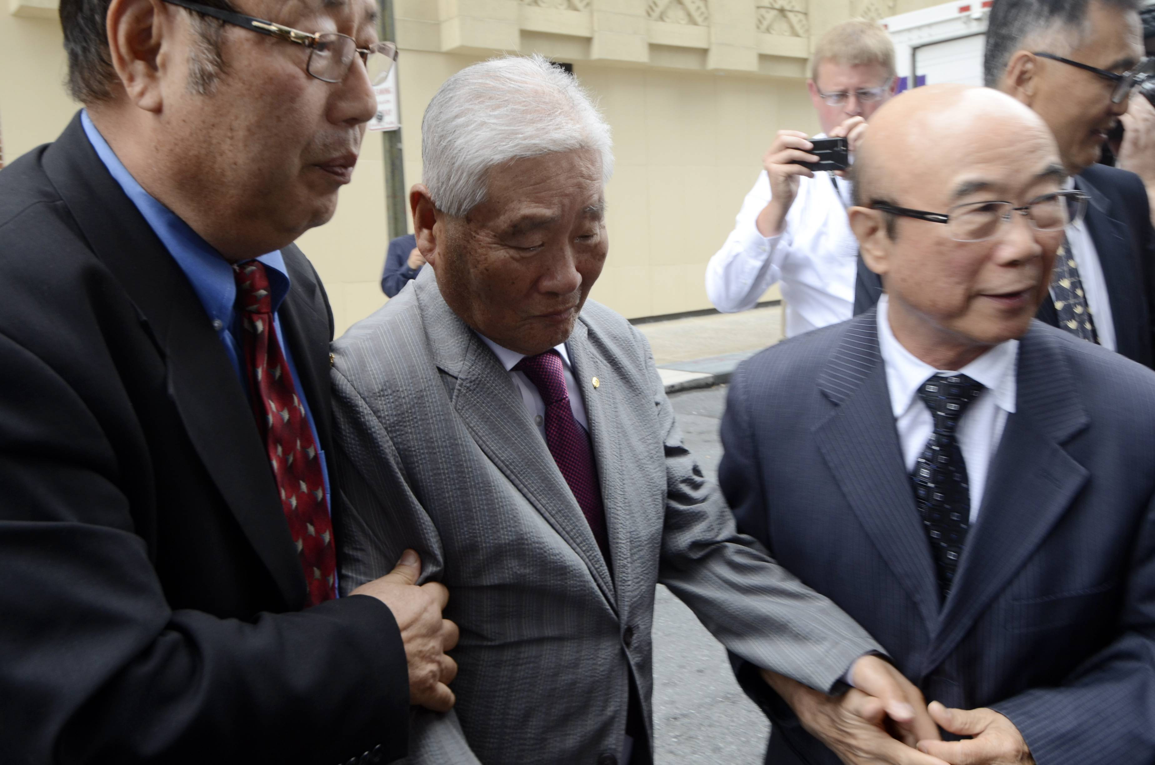Han Tak Lee, 79, arrives at the federal courthouse Friday with assistance from friends and supporters after his release from a Pennsylvania prison.