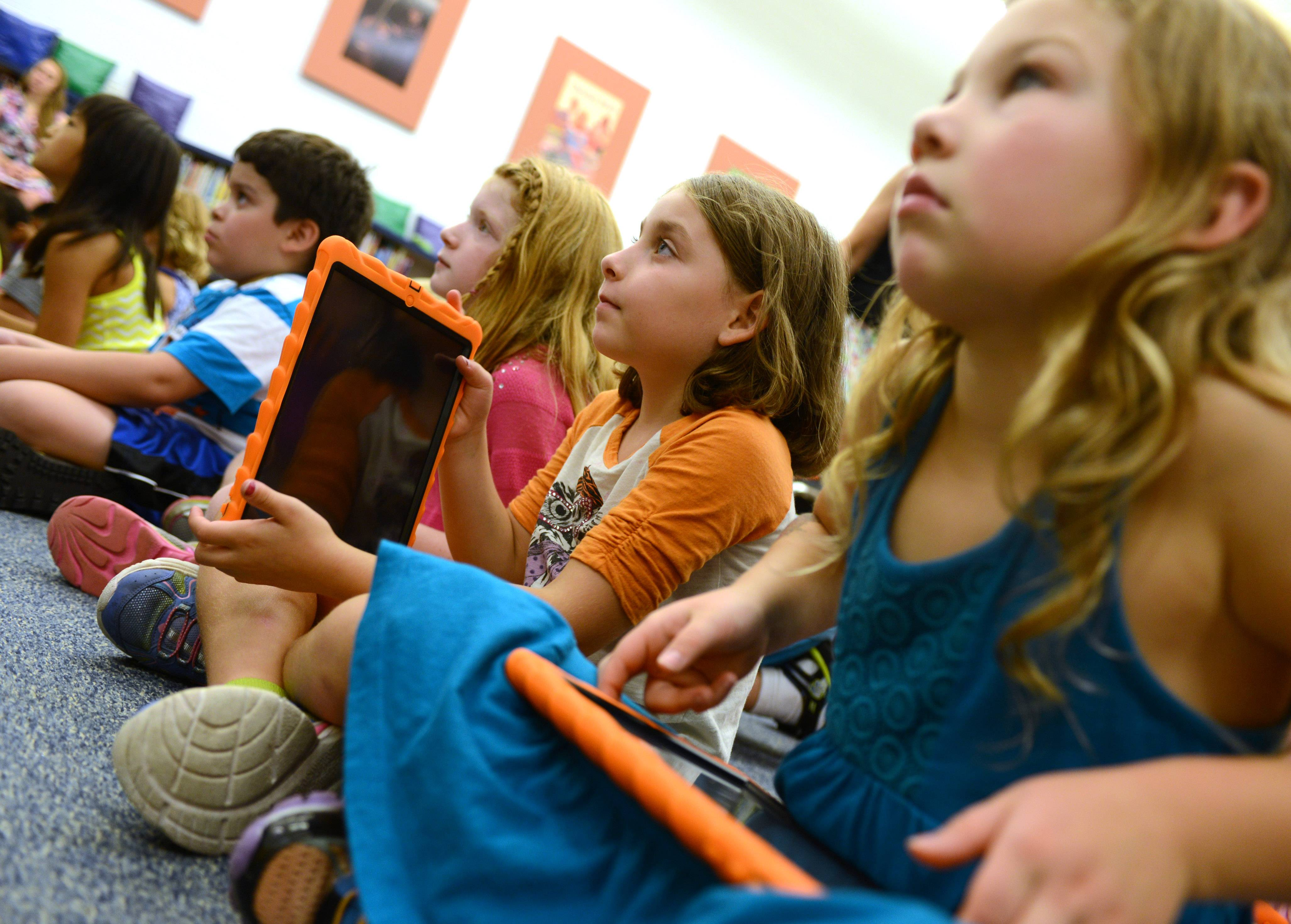 Oak Grove Elementary School third grade students Maddison Carstens, second from right, and Ava Hertsberg, right, listen during iPad instruction on first day of school Friday in Green Oaks. Students in grades kindergarten through fifth will get to use iPads in the classroom.