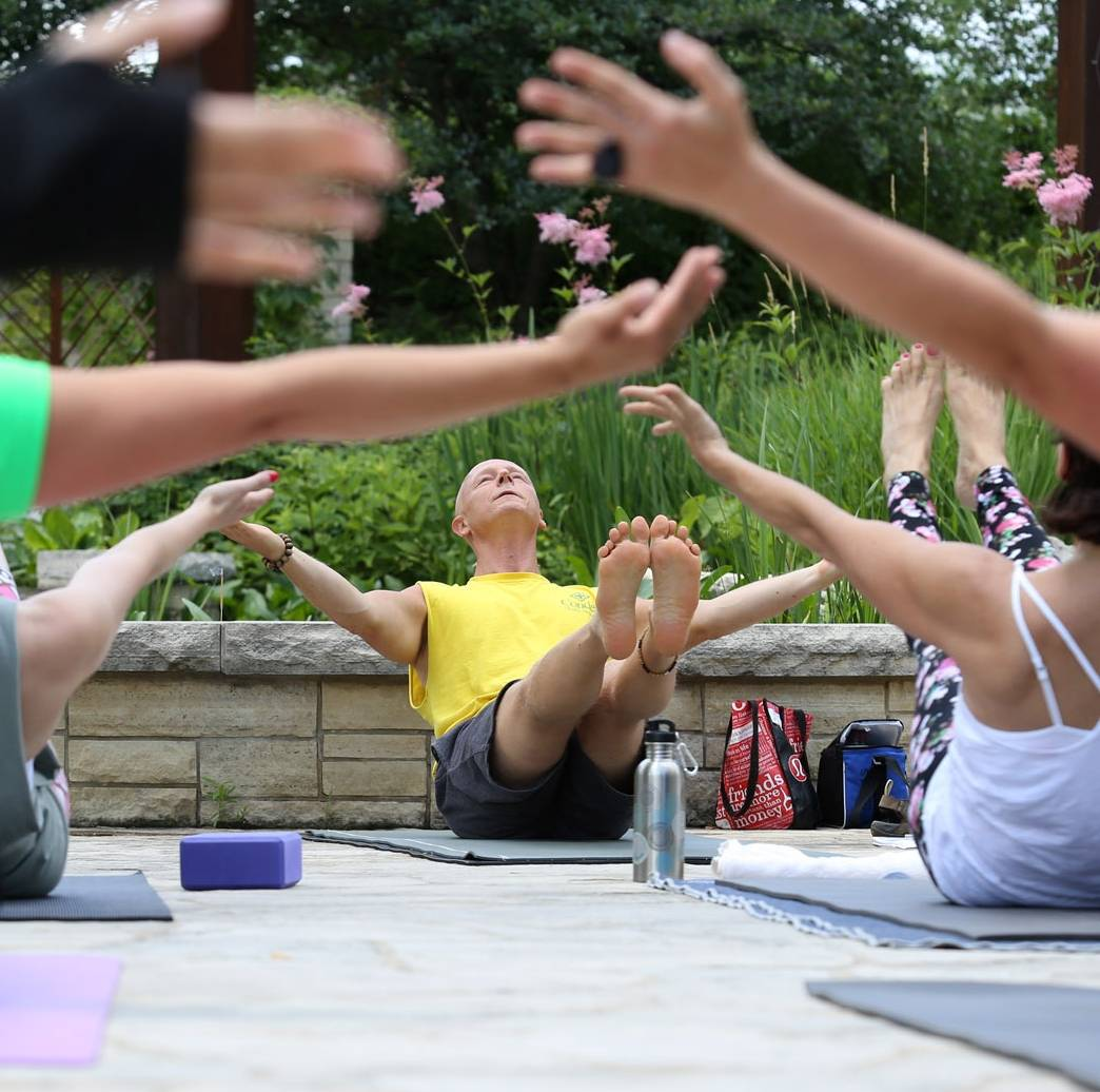 Damasius, center, instructs students to hold a boat pose at Independence Grove Forest Preserve.