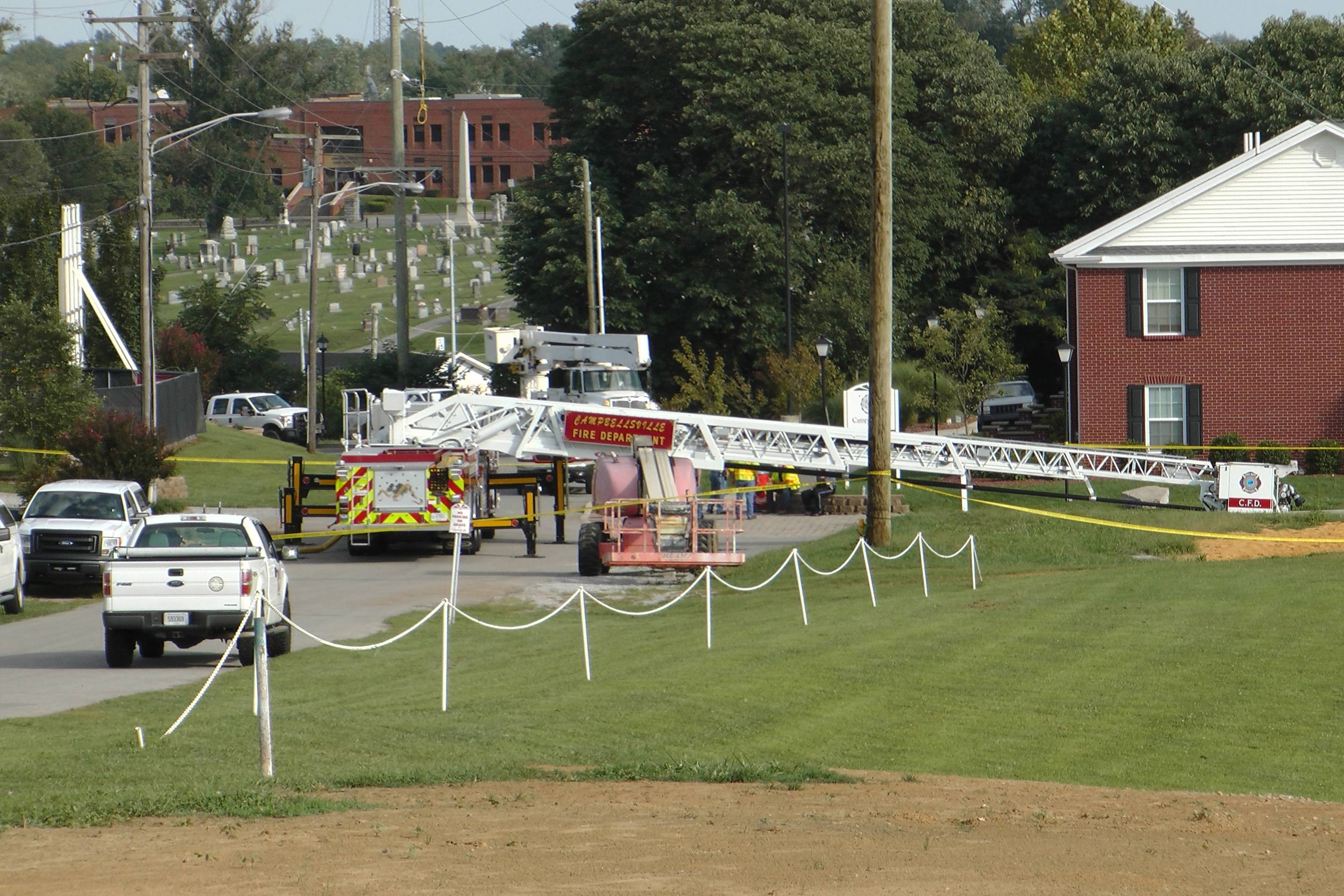 A Campbellsville Fire Department truck with the ladder extended remained at the scene where two firefighters were injured during an ice bucket challenge during a fundraiser for ALS on Thursday, Aug. 21, 2014, in Campbellsville, Ky. Officials say the ladder got too close to a power line and electricity traveled to the ladder, electrocuting the firefighters.