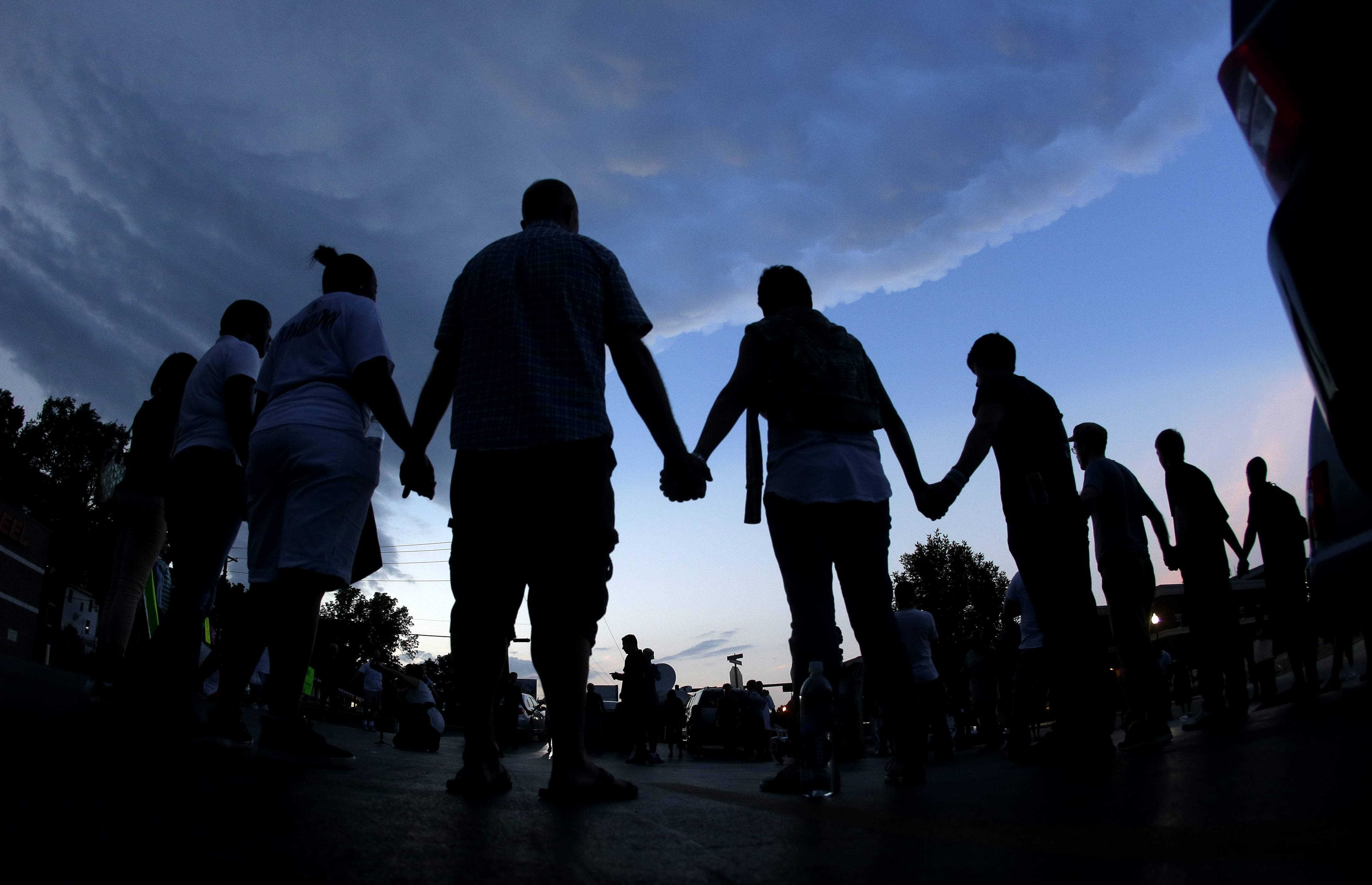 People stand in prayer Wednesday after marching about a mile to the police station to protest the shooting of Michael Brown in Ferguson, Mo. Brown's shooting in the middle of a street Aug 9, by a Ferguson policeman has sparked a more than week of protests, riots and looting in the St. Louis suburb.