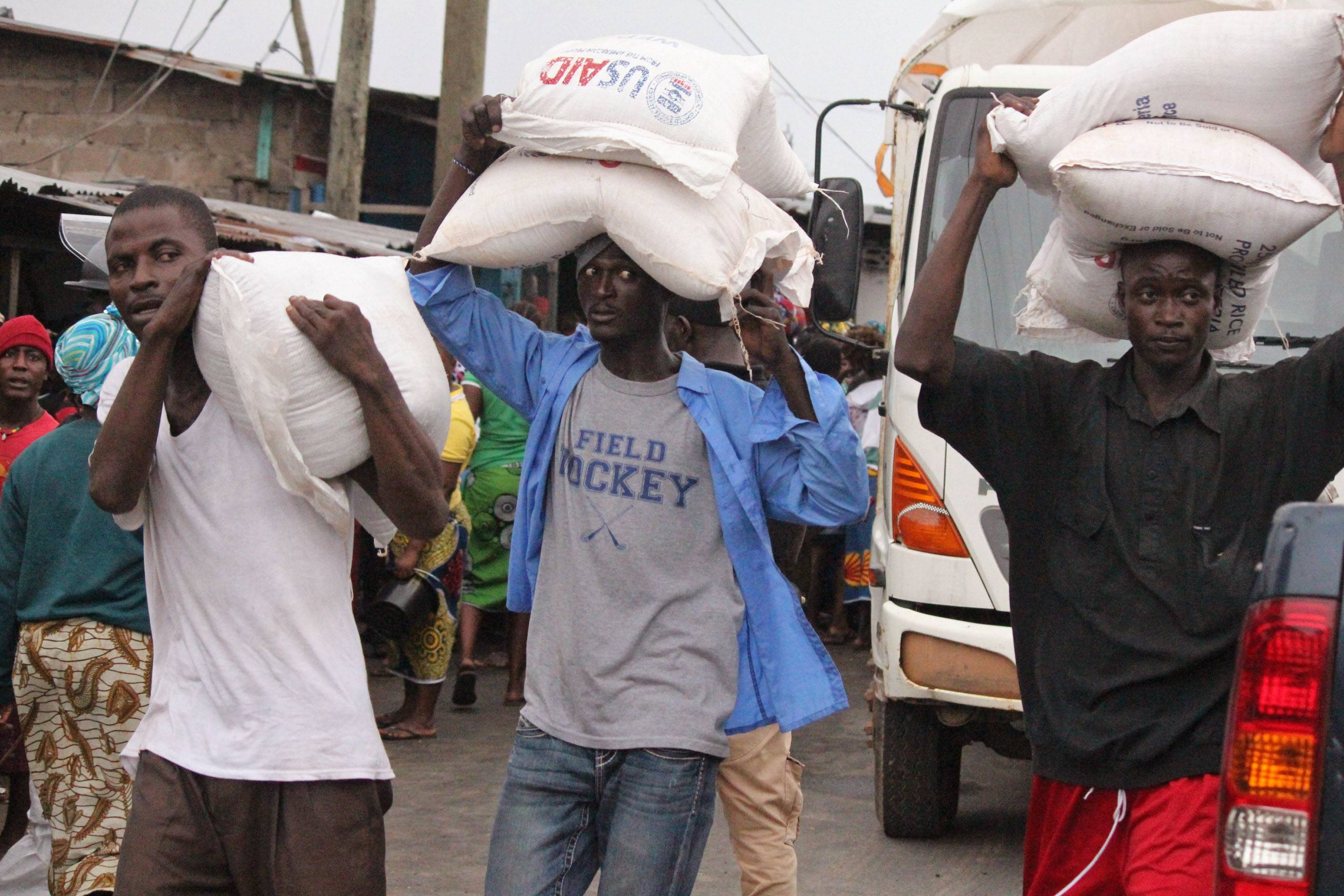 Men carry food aid that was given to them Thursday at the West Point area, one of the places where the Ebola virus has claimed lives, in Monrovia, Liberia. Calm returned Thursday to a slum in the Liberian capital that was sealed off in the government's attempt to halt the spread of Ebola, a day after clashes erupted between residents and security forces, but now the tens of thousands of residents worried about getting food.