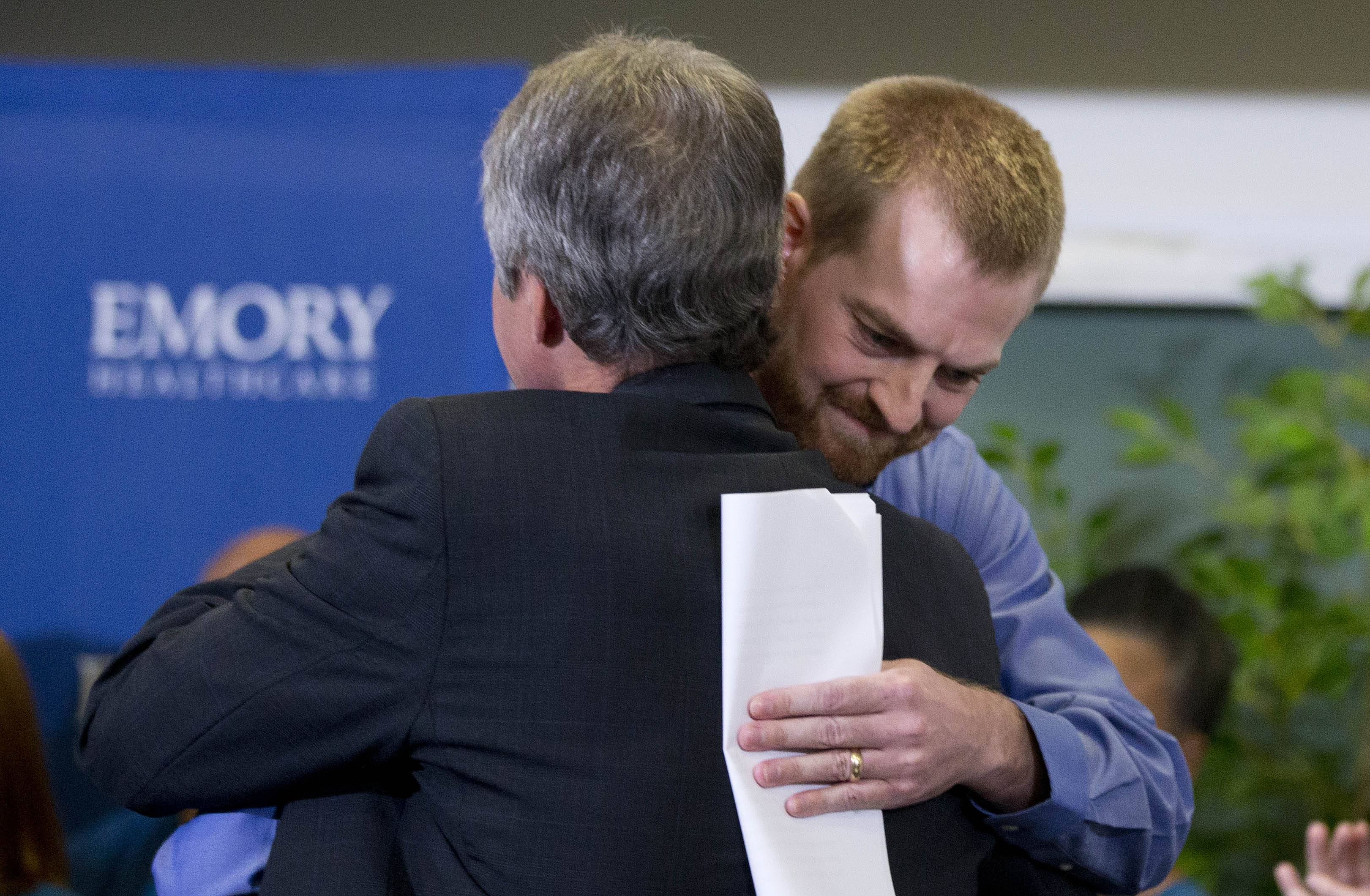 Ebola victim Dr. Kent Brantly, right, hugs a member of the medical staff that treated him, after being released Thursday from Emory University Hospital in Atlanta. Another American aid worker, Nancy Writebol, who was also infected with the Ebola virus, was released from the hospital Tuesday.