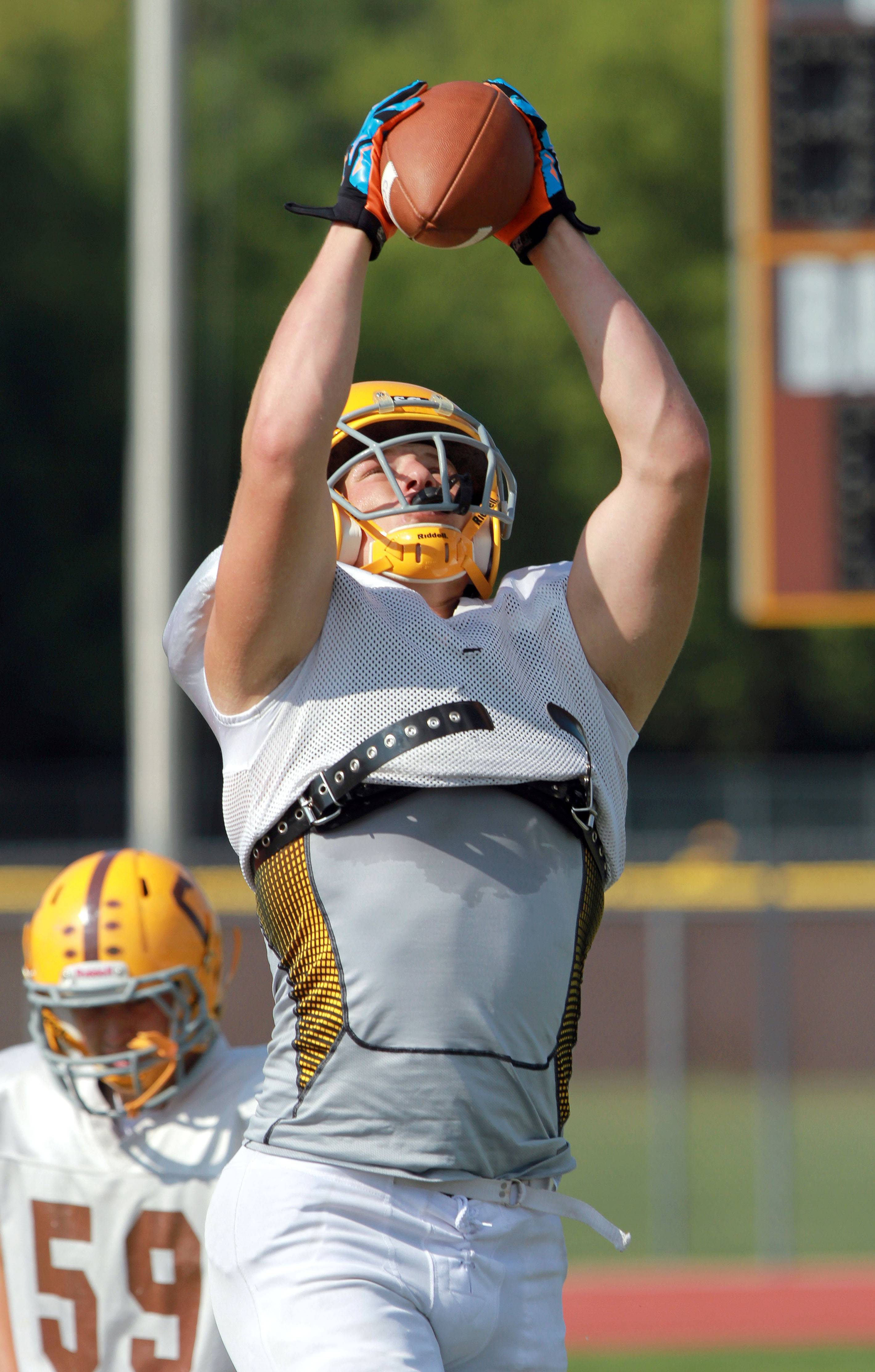 TE Noah Turner goes up for a catch during football practice Tuesday at Carmel High School in Mundelein.