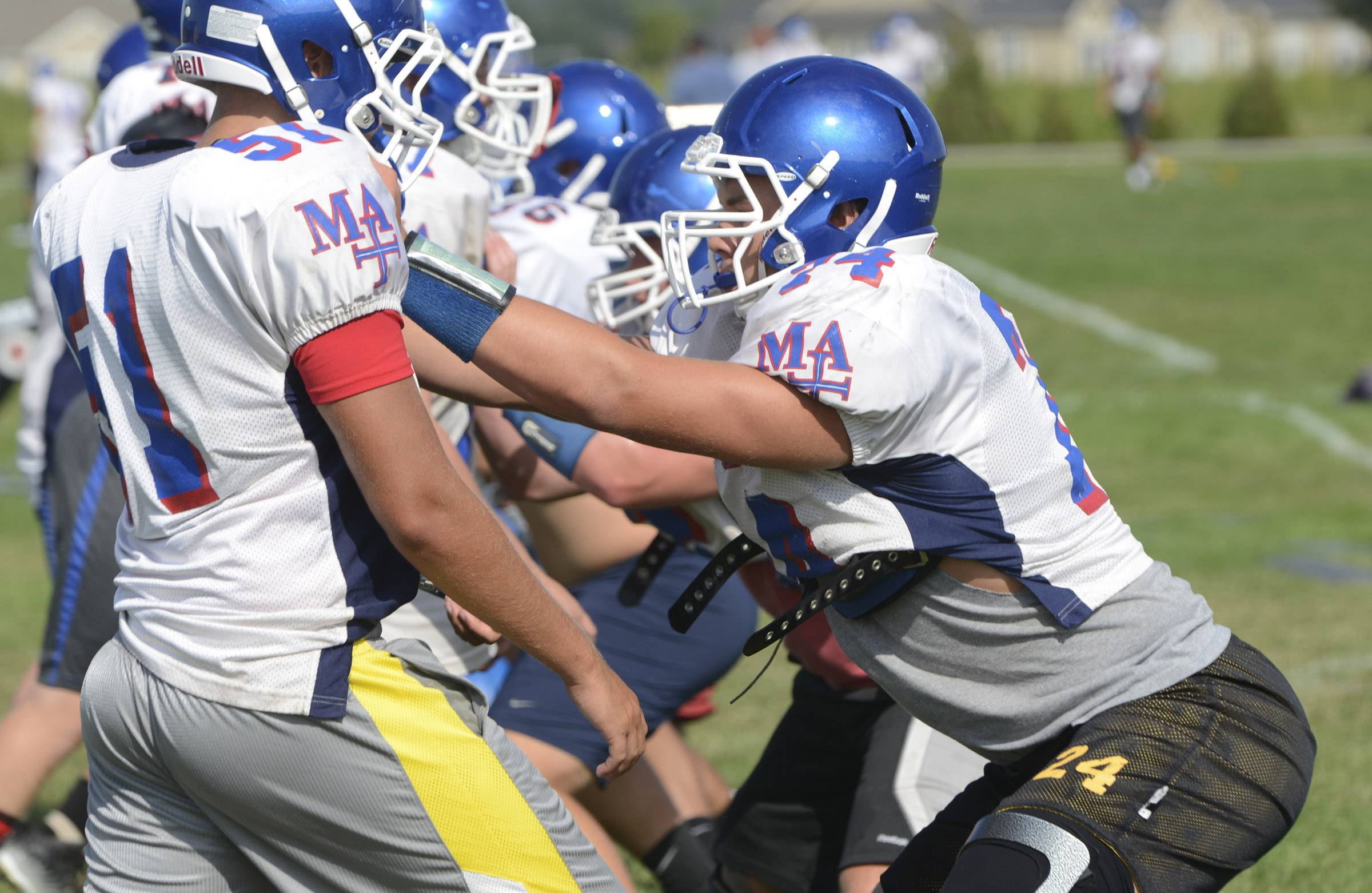 Tackle John Gauthier, right, works on a blocking drill Thursday at the Marmion Academy football practice in Aurora.