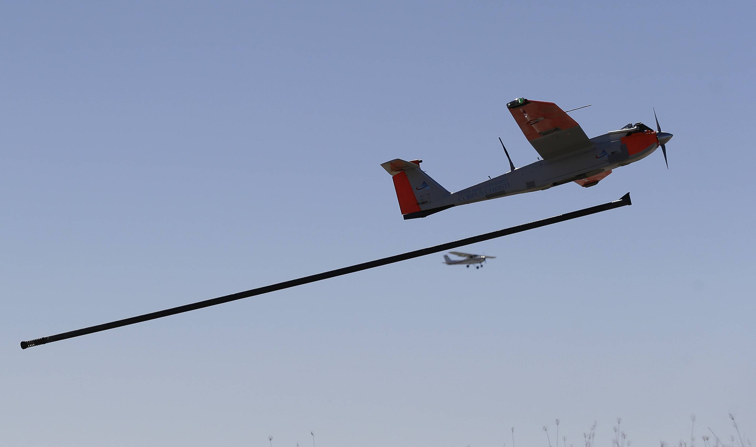 A test drone as it is is launched by catapult as a trail plane follows on a ranch near Sarita, Texas.