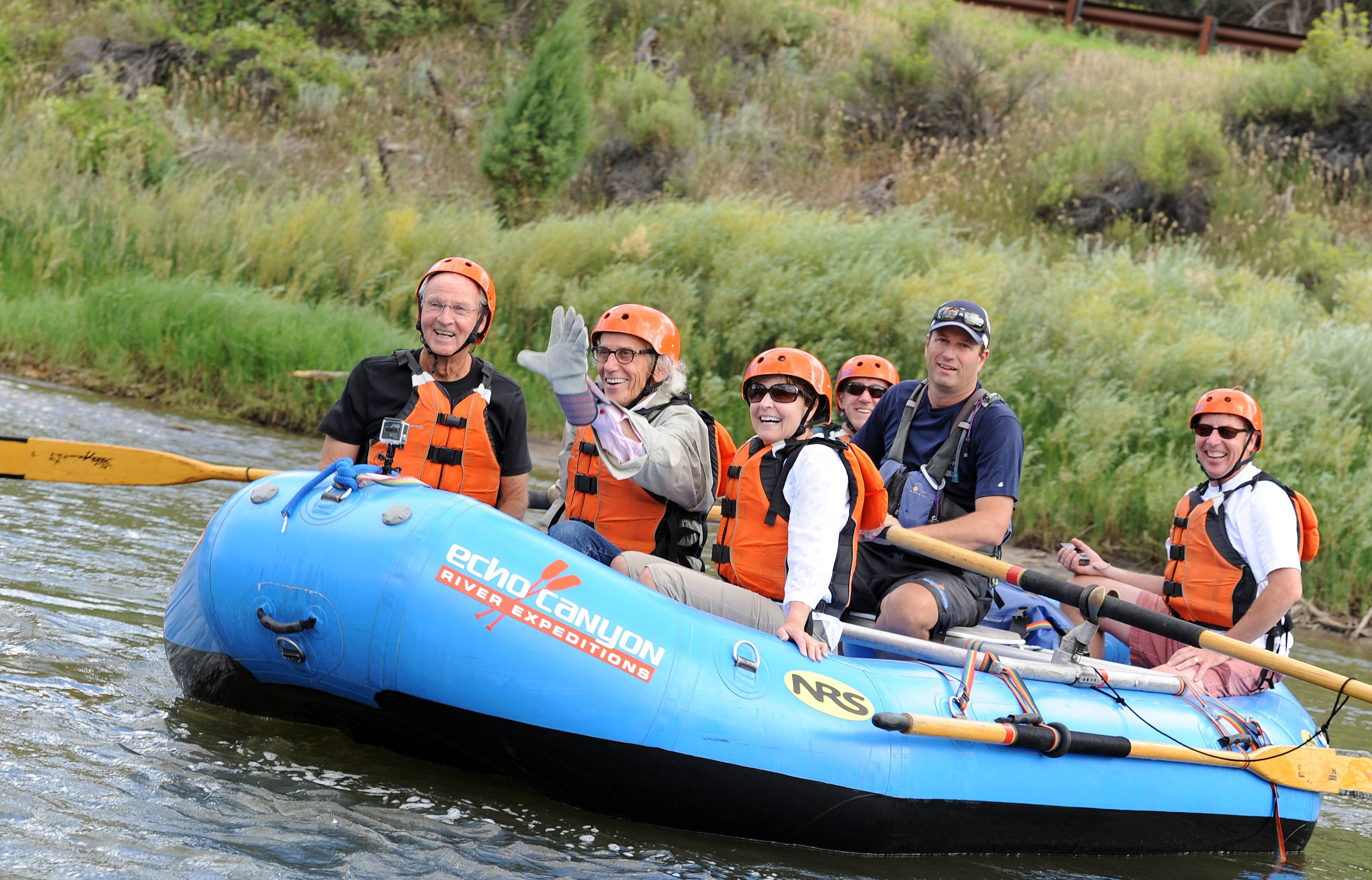 Artist Christo, second from left, waves as he rafts with associates, a journalist, and a river guide Thursday along the Arkansas River from Spike Buck to Parkdale, Colo.